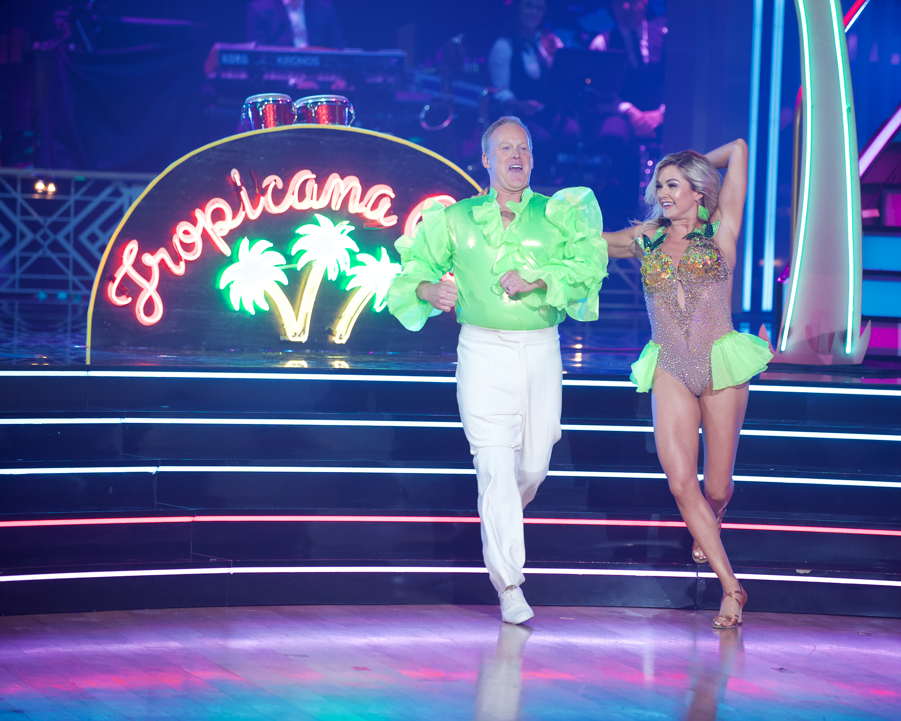 "Sean Spicer dancing with a partner onstage on ""Dancing With the Stars"" with a neon Tropicana backdrop with palm trees."