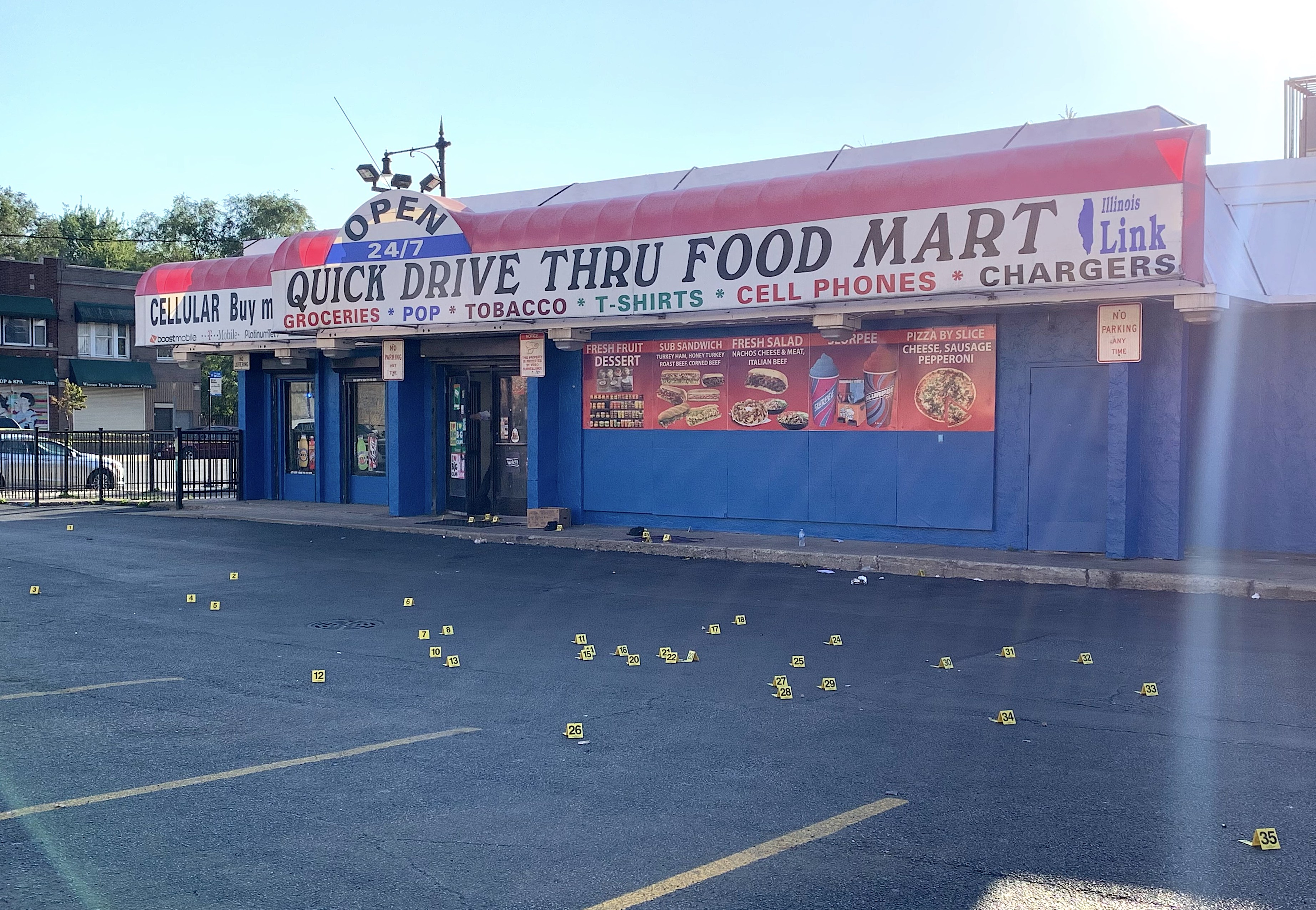 At least 40 evidence markers were laid out where four men were shot in front of a West Garfield Park store on Sept. 18, 2019. | Jake Wittich/Sun-Times
