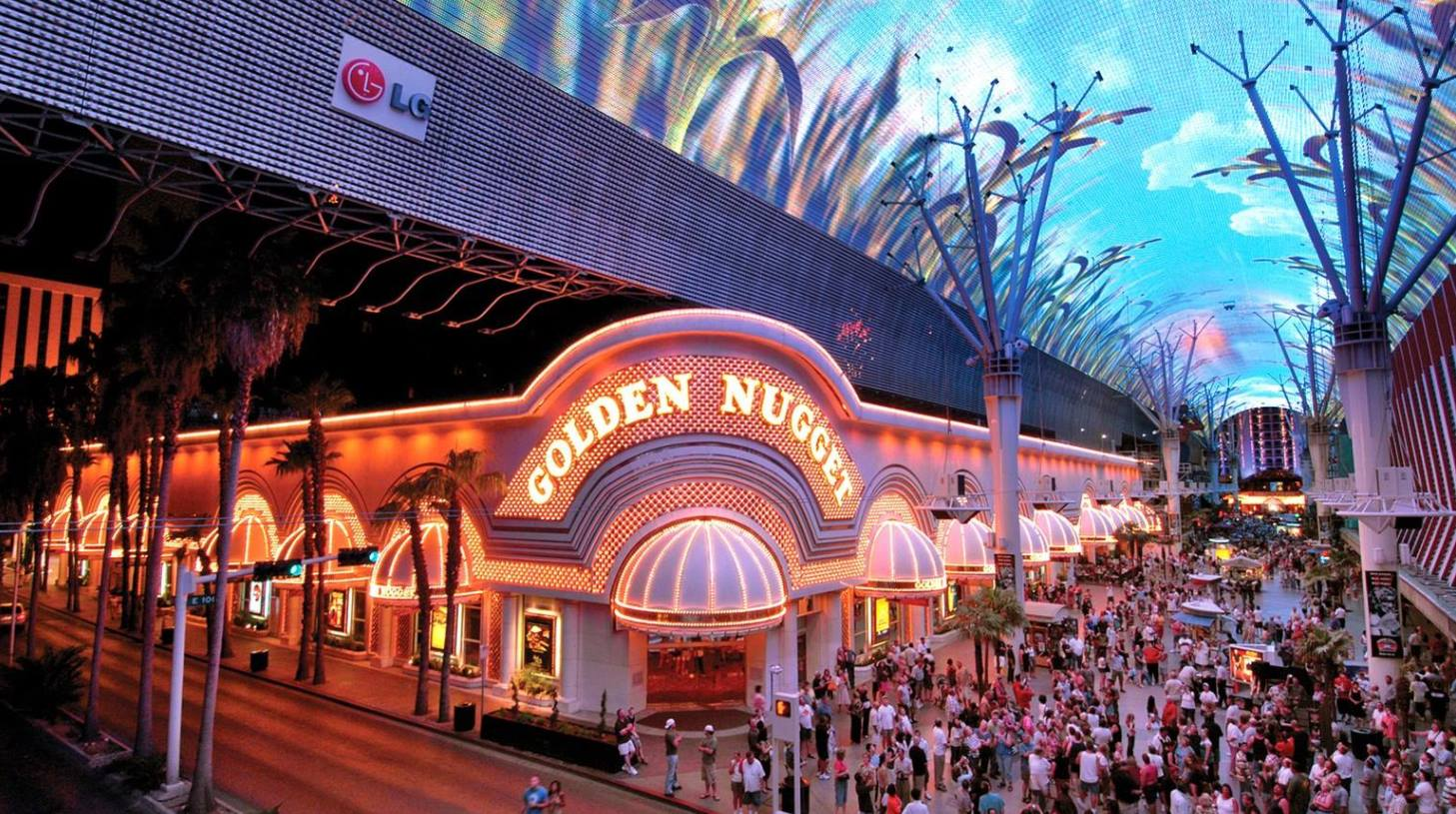 The busy western corner entrance and bright signage of the Golden Nugget Las Vegas resort on downtown's Fremont Street.