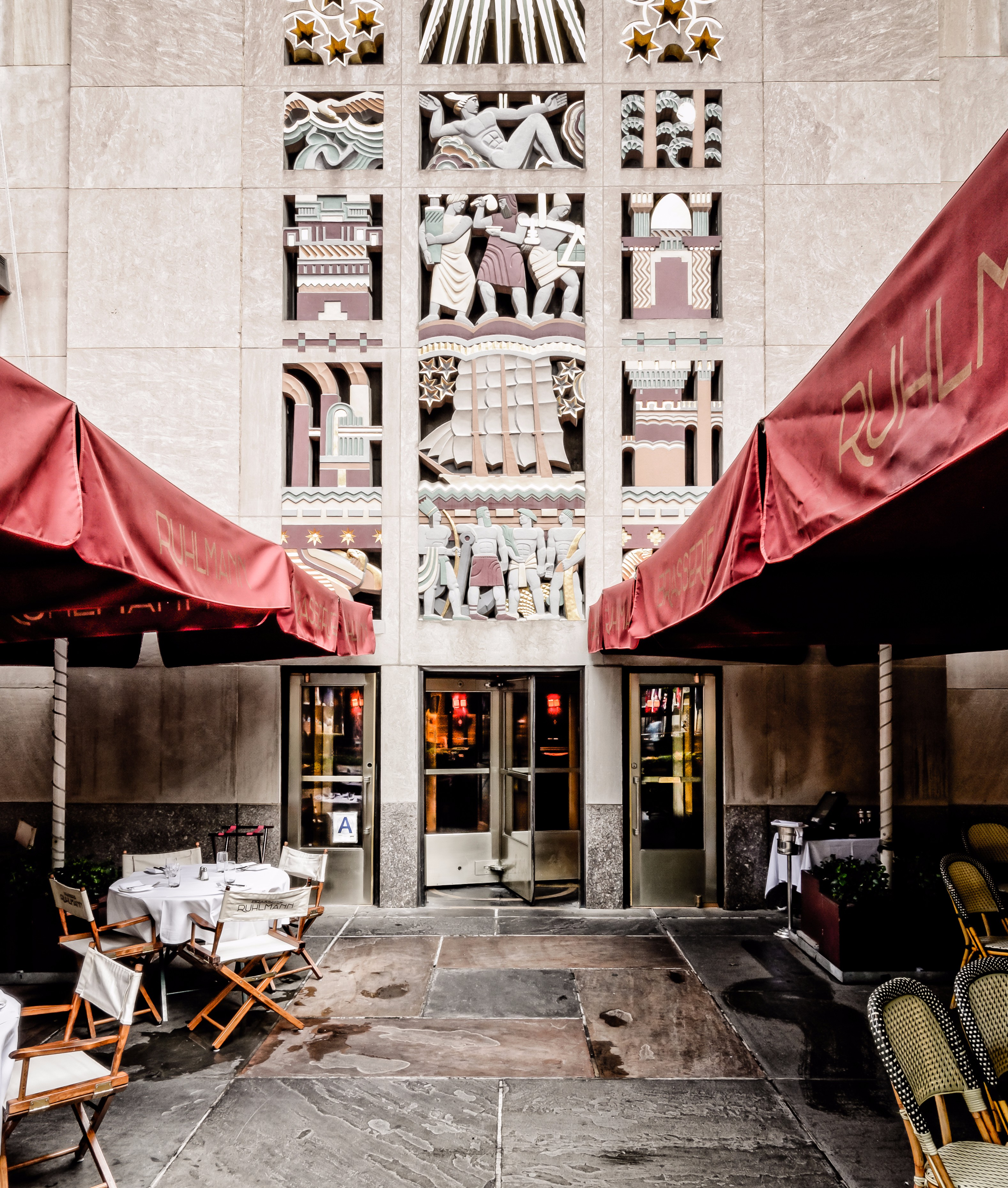 The entrance of Brasserie Ruhlmann in an art deco building with red awnings