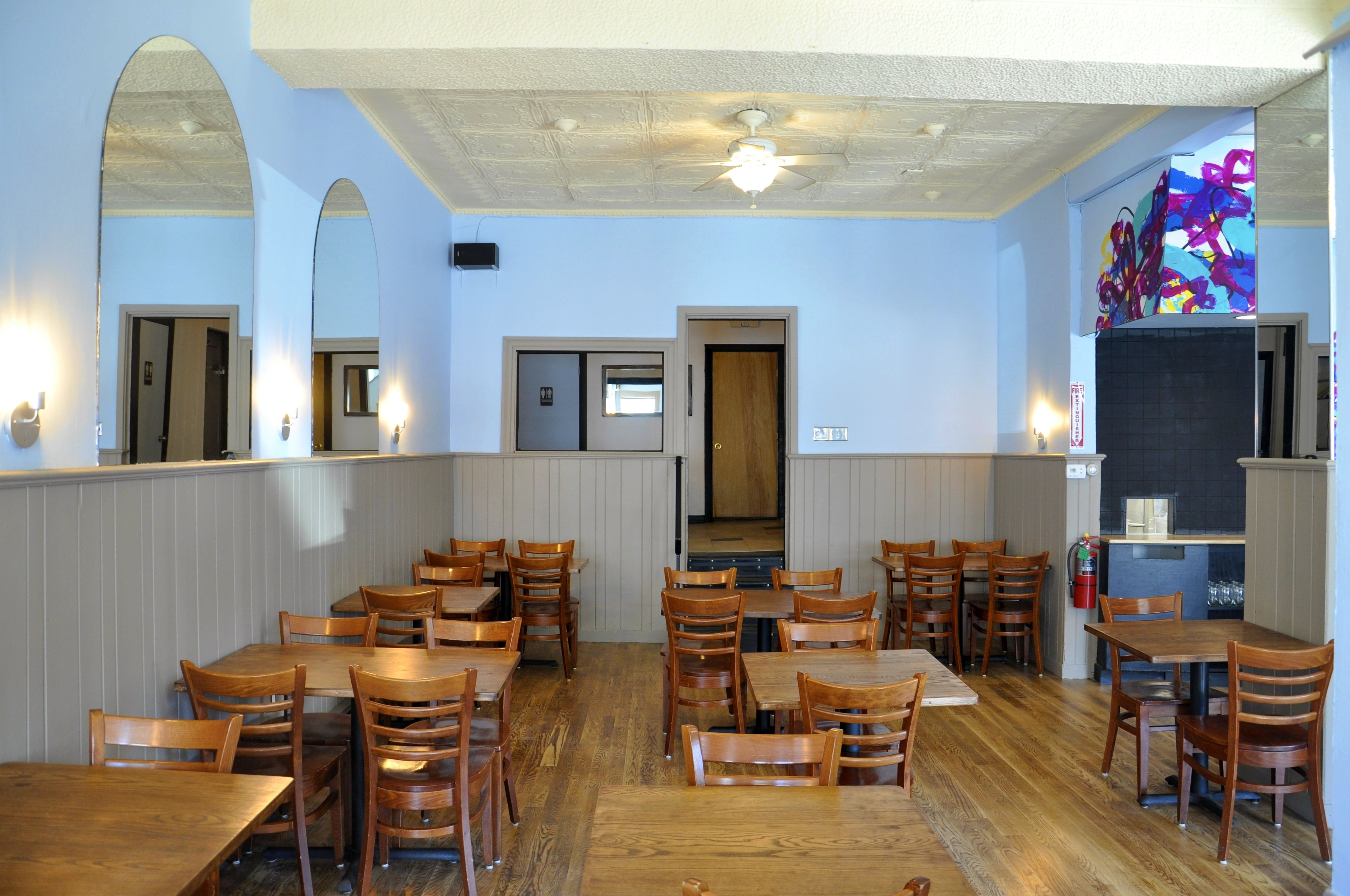 Wide view of a restaurant space with wooden floors and tables, tan-colored wood paneling on the lower half of the walls and light blue-painted walls above