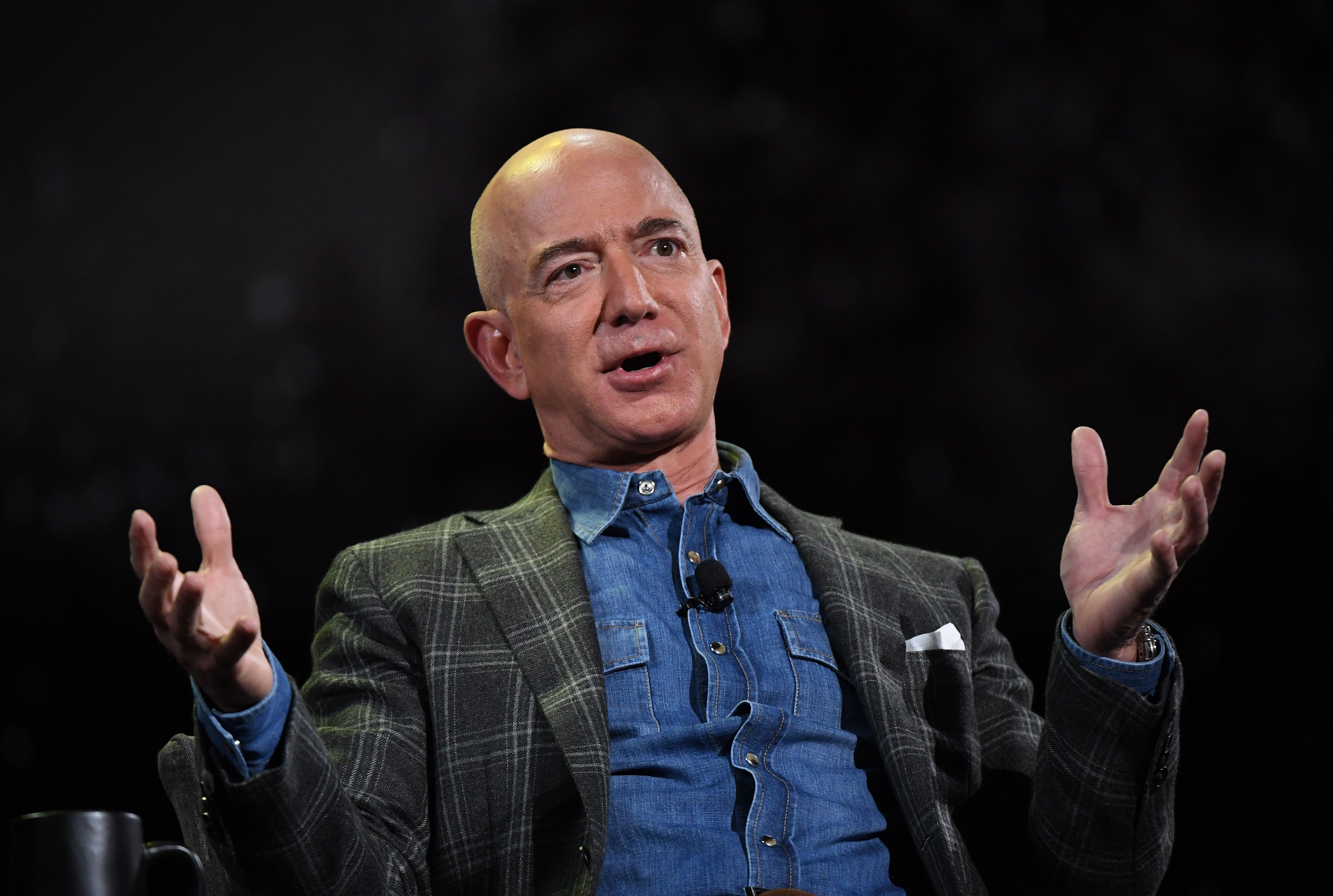 Amazon CEO Jeff Bezos gesticulating while speaking onstage at a company event.