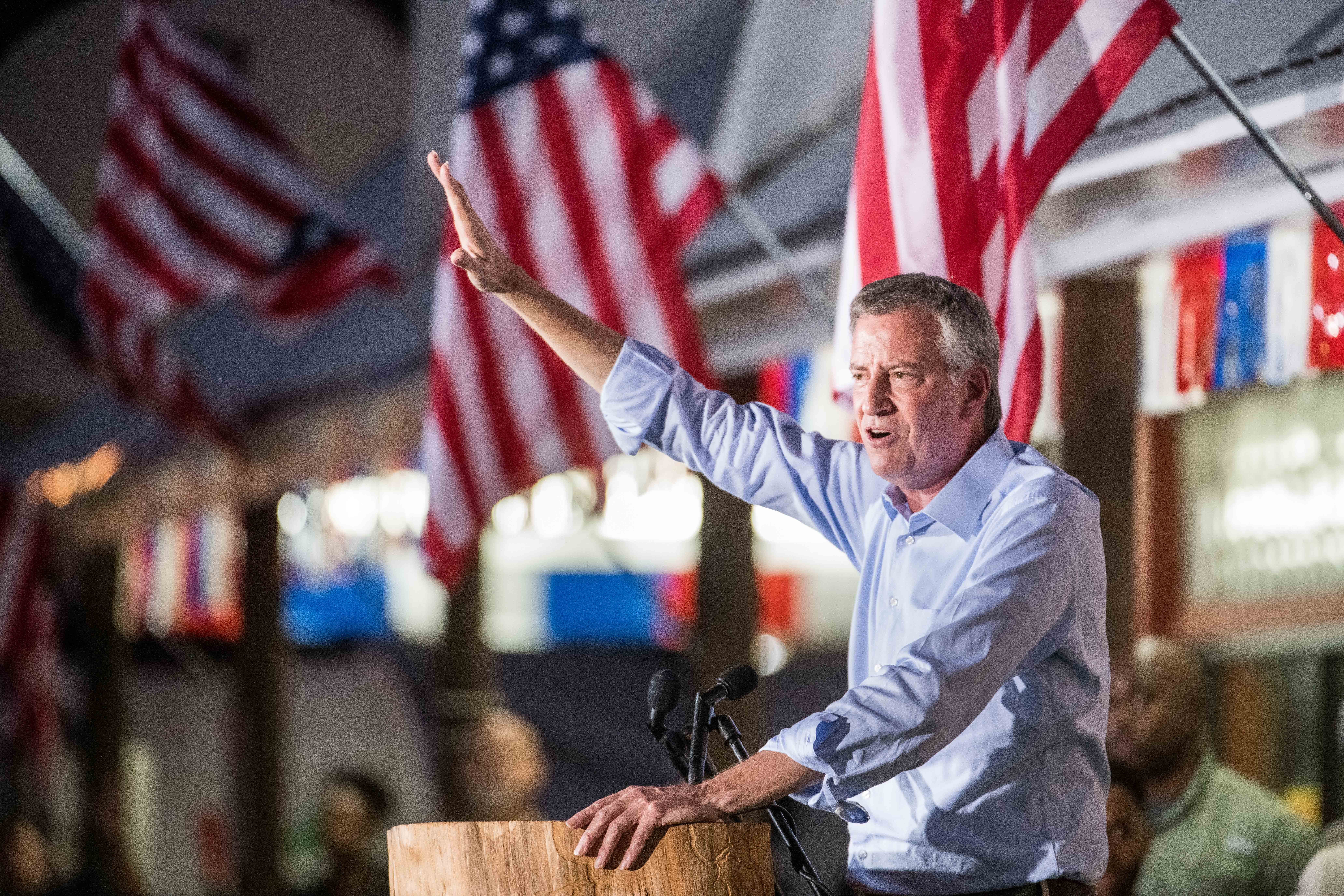 Democratic presidential candidate and New York City Mayor Bill de Blasio stands speaking from behind a podium with one arm raised. Behind him are several America flags.