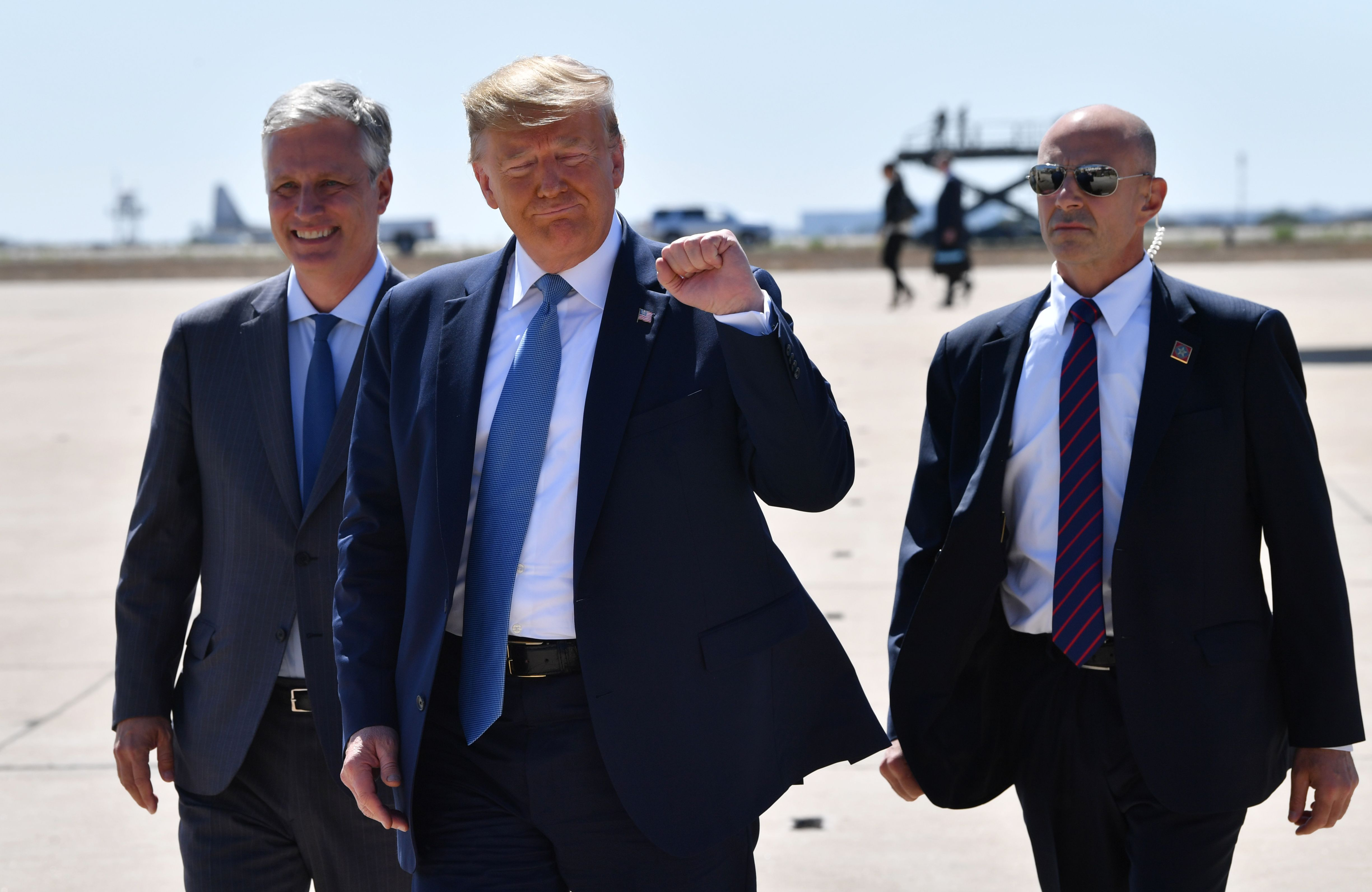 President Donald Trump, holding up a fist, walks from his plane to his car  with two other men at the San Diego airport.