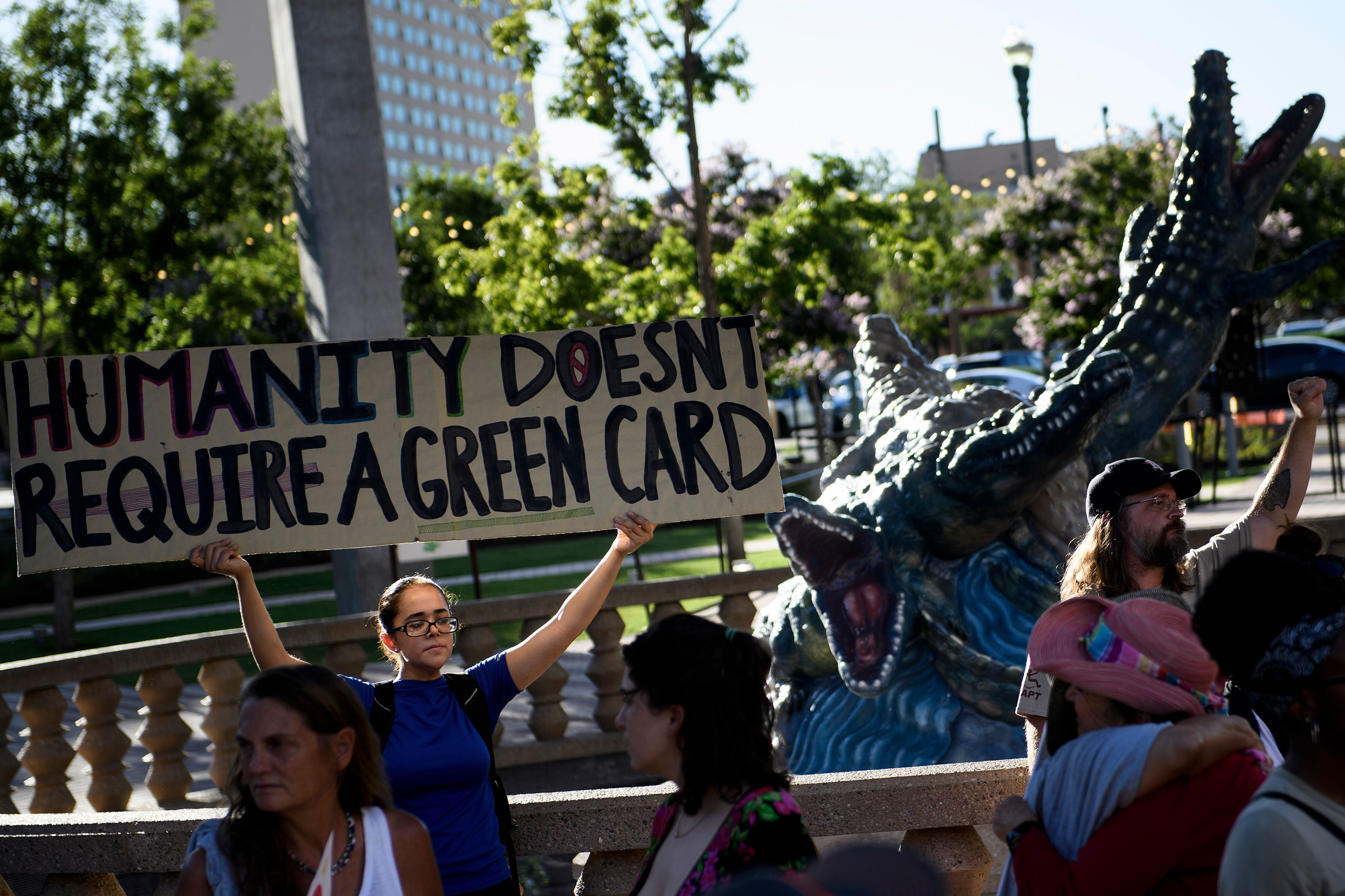 "An activist holds up a large sign that reads, ""Humanity doesn't require a green card."""