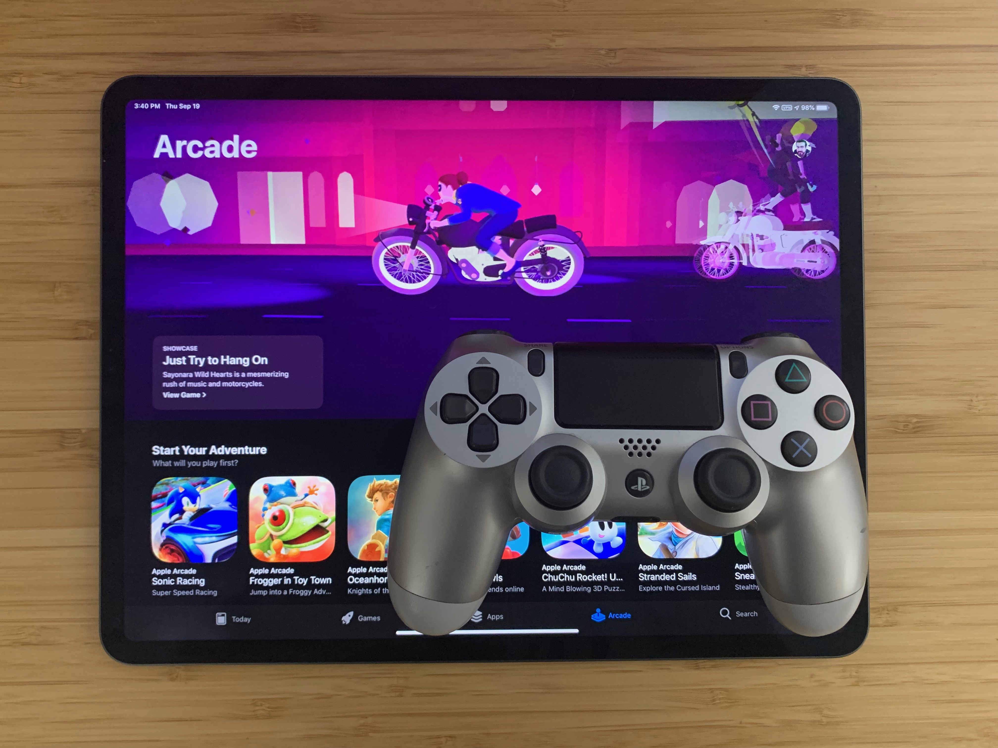 """A DualShock 4 controller sits on a 12.9"""" iPad Pro (2018) displaying the Apple Arcade home screen"""