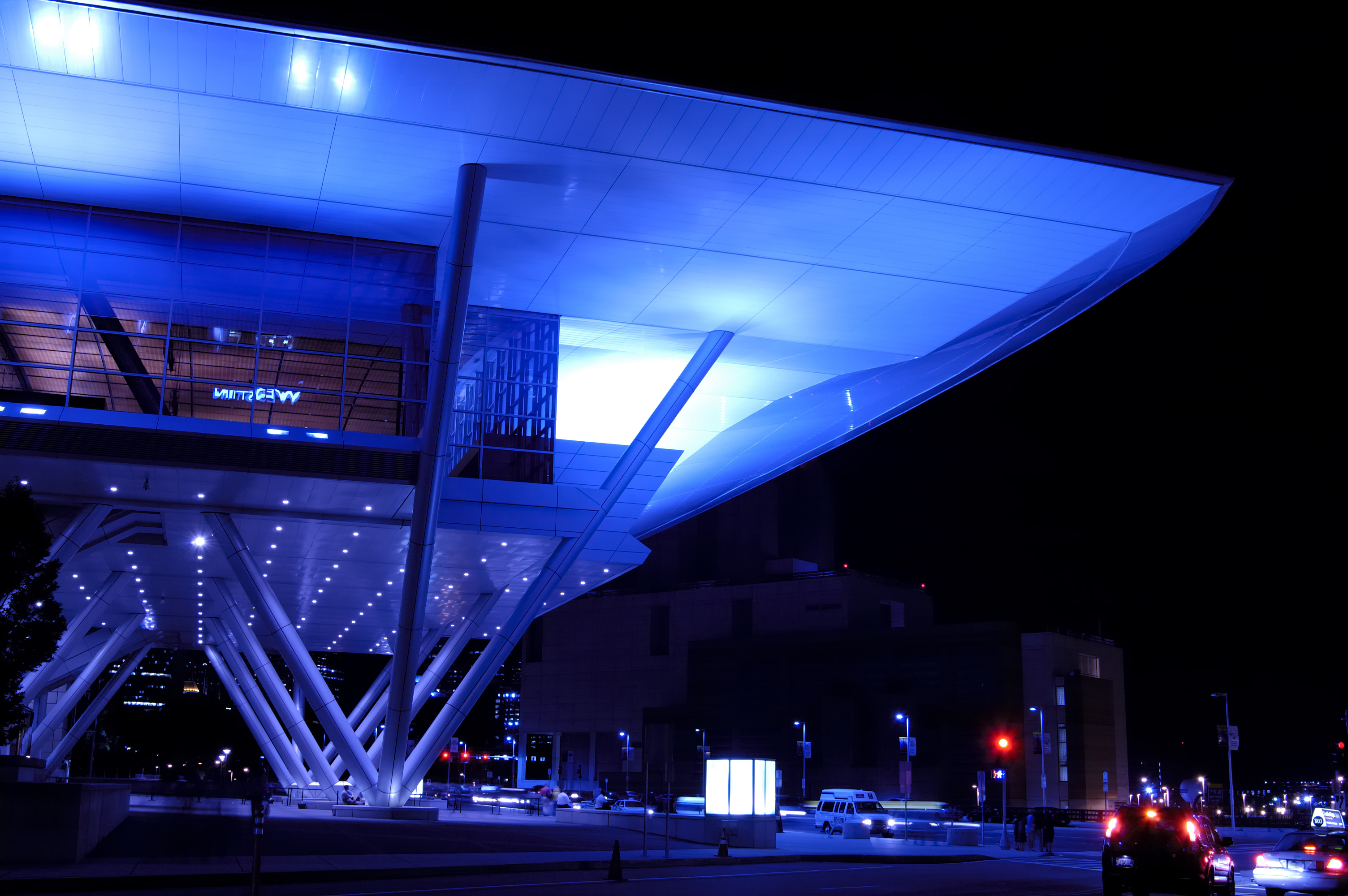 The glowing exterior of a major convention center at night.