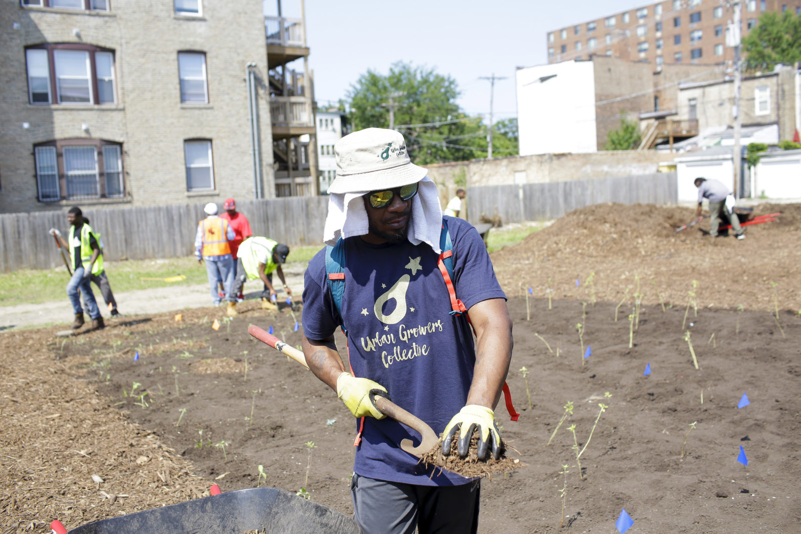 Ashanti Randolph (above) from Urban Growers Collective places mulch around freshly planted sunflowers in one of the lots, in the 6000 block of South Dr. Martin Luther King Jr. Drive.