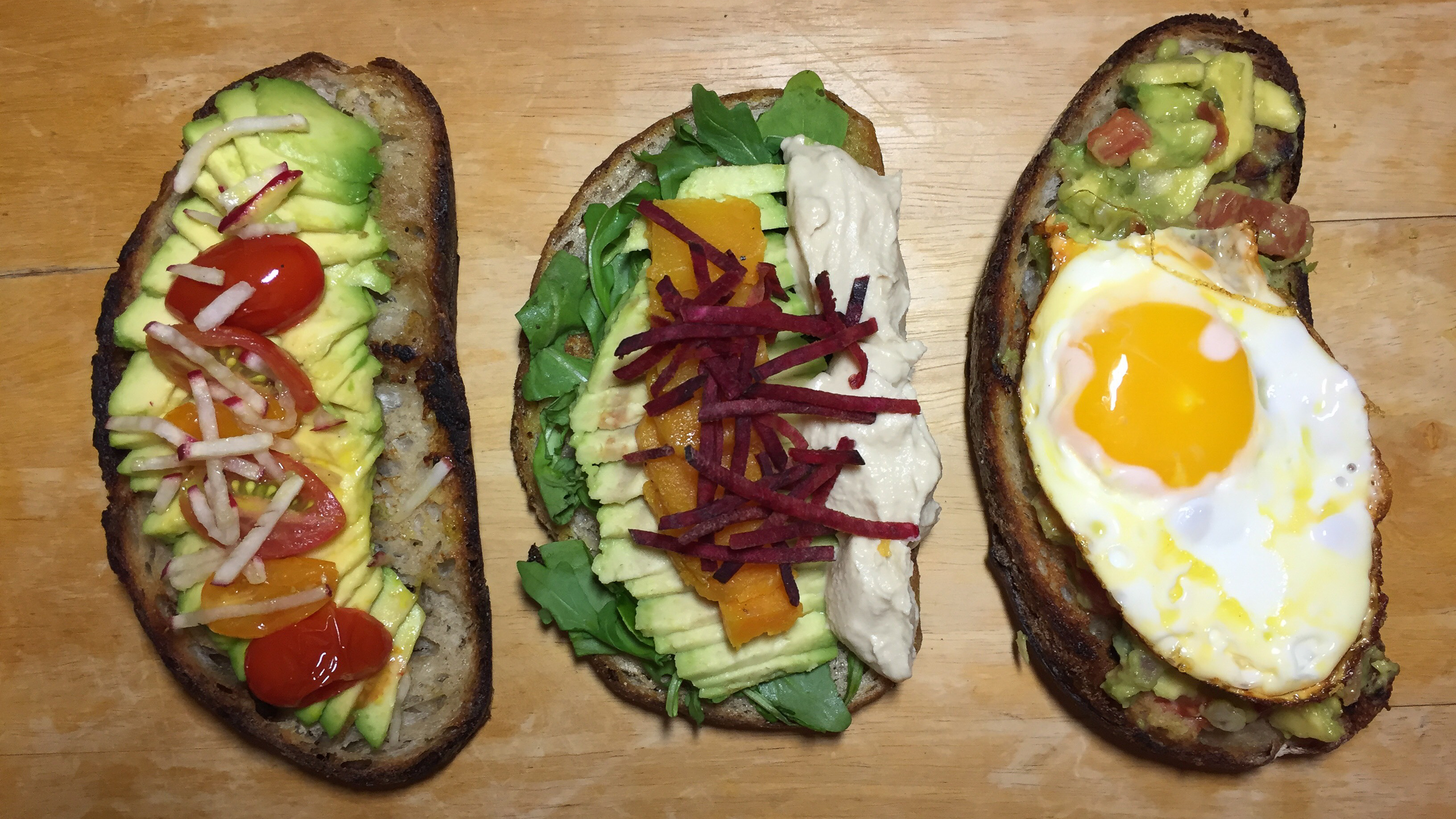 Three slices of bread side by side come topped with avocado and other ingredients, including tomatoes, beets, and a sunny-side egg