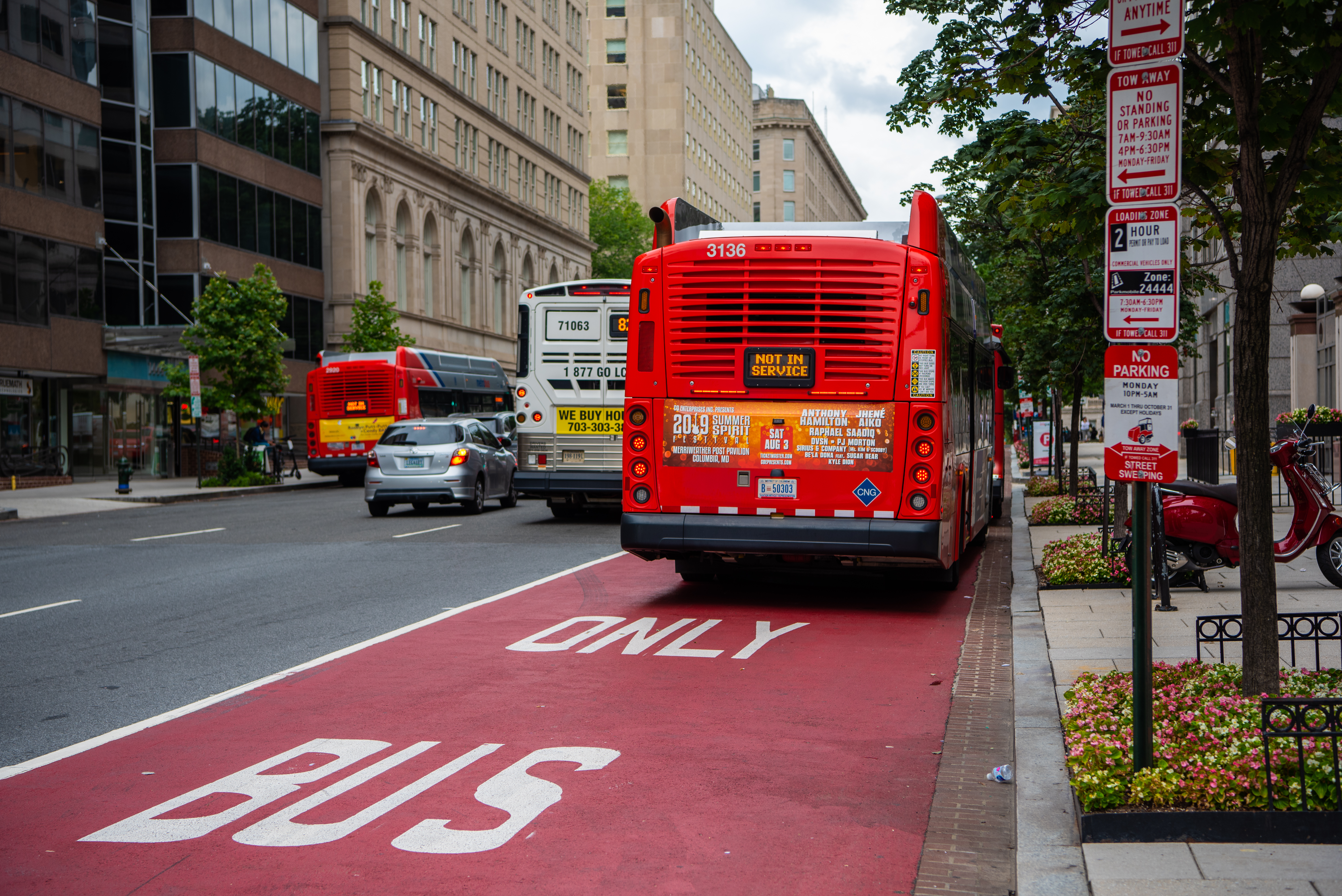 "A bus seen from behind in a ""bus only"" lane painted red in the midst of a city."