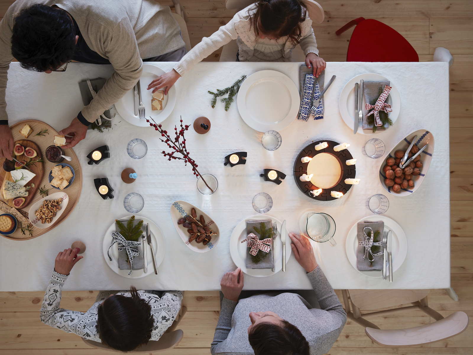 A family sitting around dinner table with white dinnerware and black candleholders.