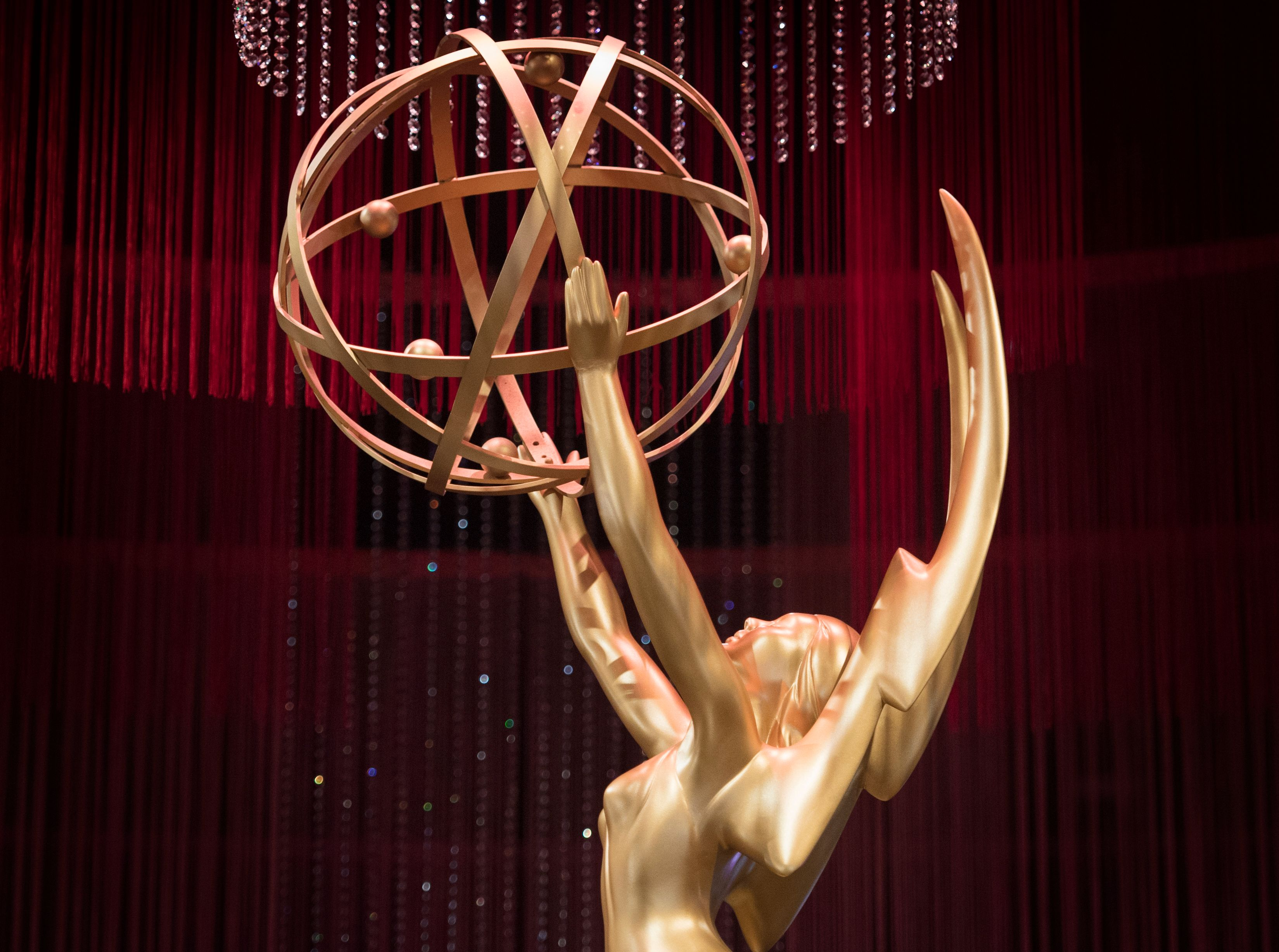 The Emmy statuette is a female figure with wings holding up a ball representing rotating electrons.