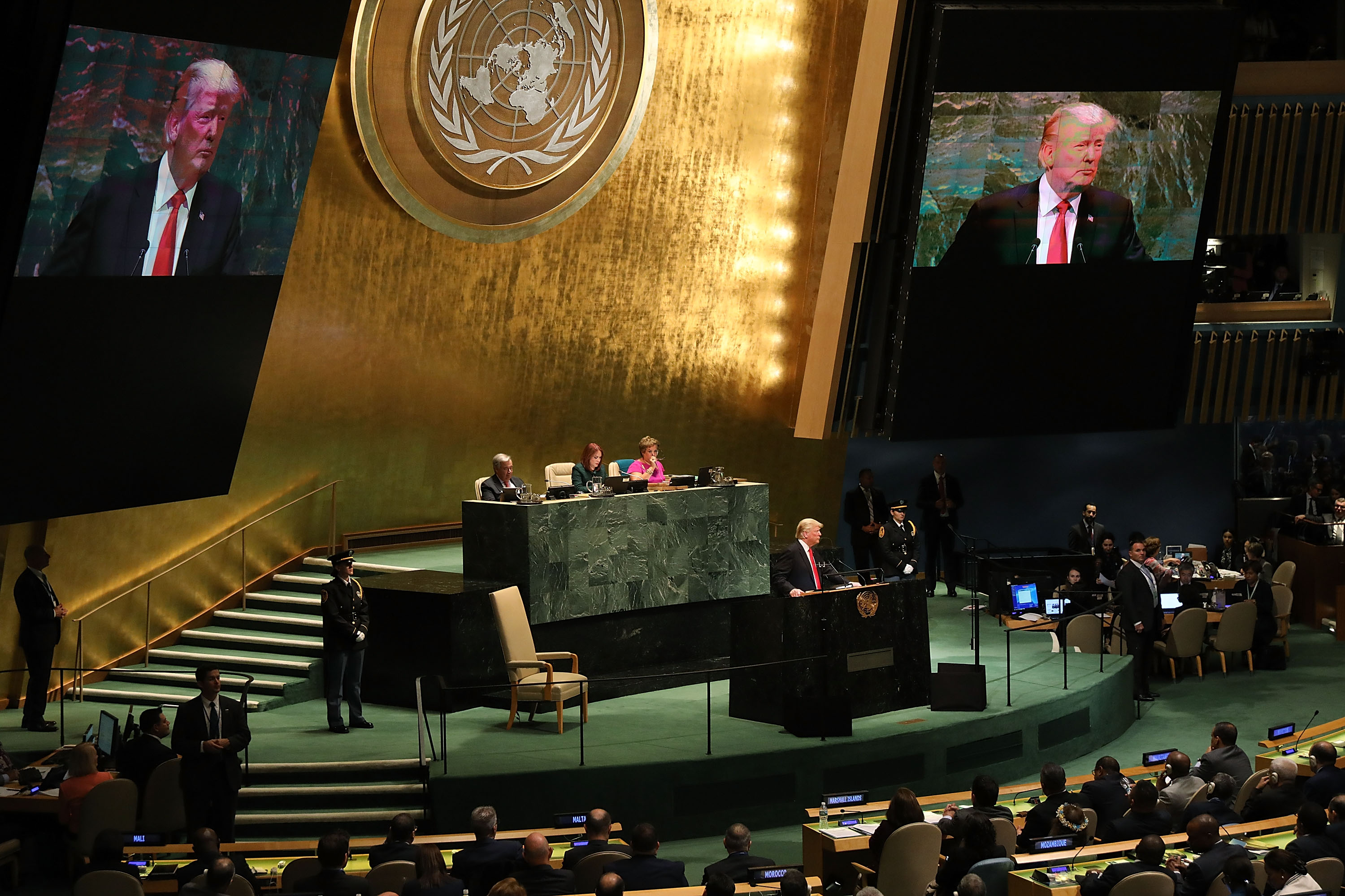 President Donald Trump addresses the United Nations General Assembly from behind a podium. Huge screens to either side project his image to the seated members.