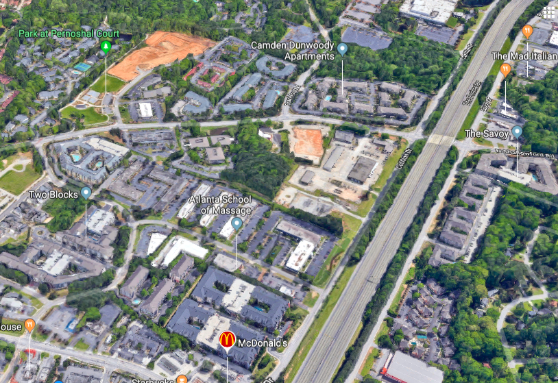 An aerial view of apartments and highways and woods north of Atlanta.