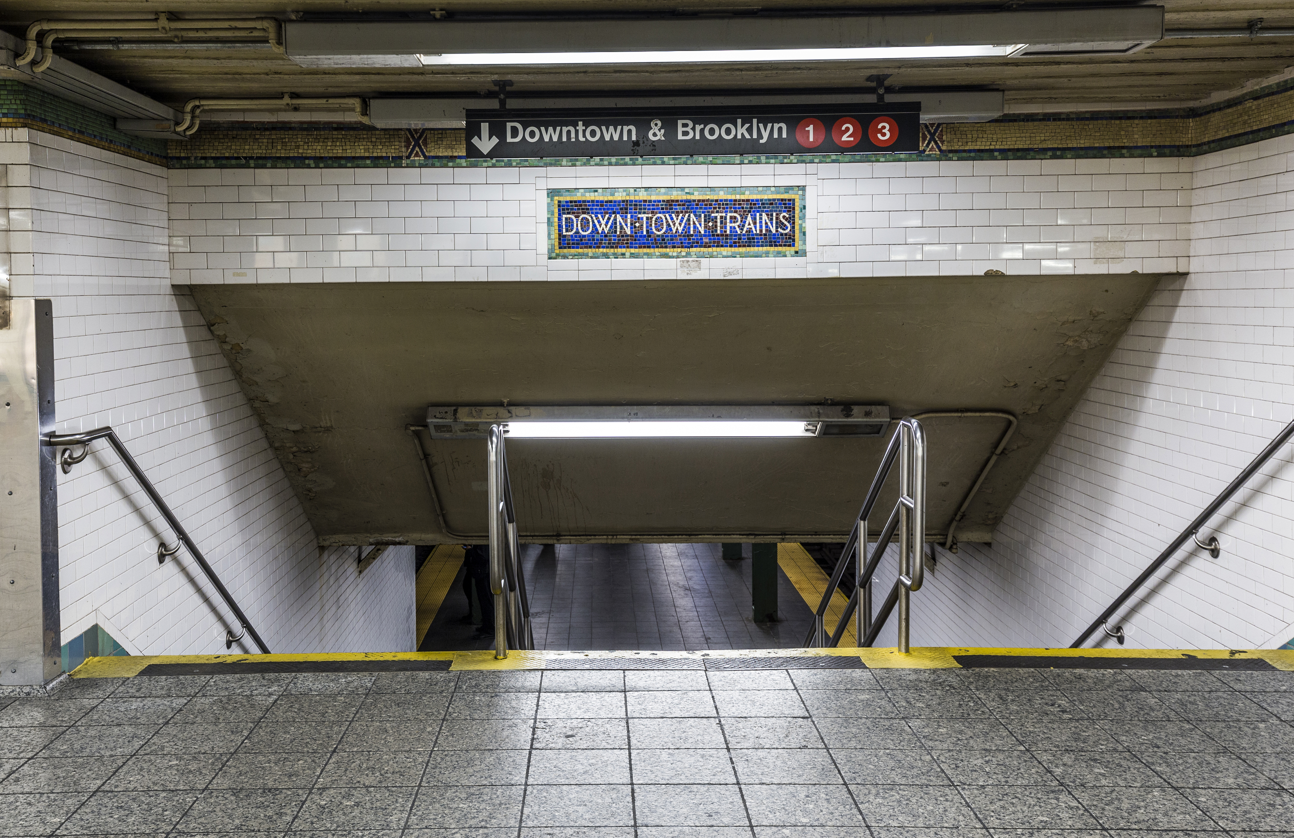 """A staircase that leads to a train platform at a NYC subway station. A sign says """"Downtown & Brooklyn"""" with an arrow pointing down."""