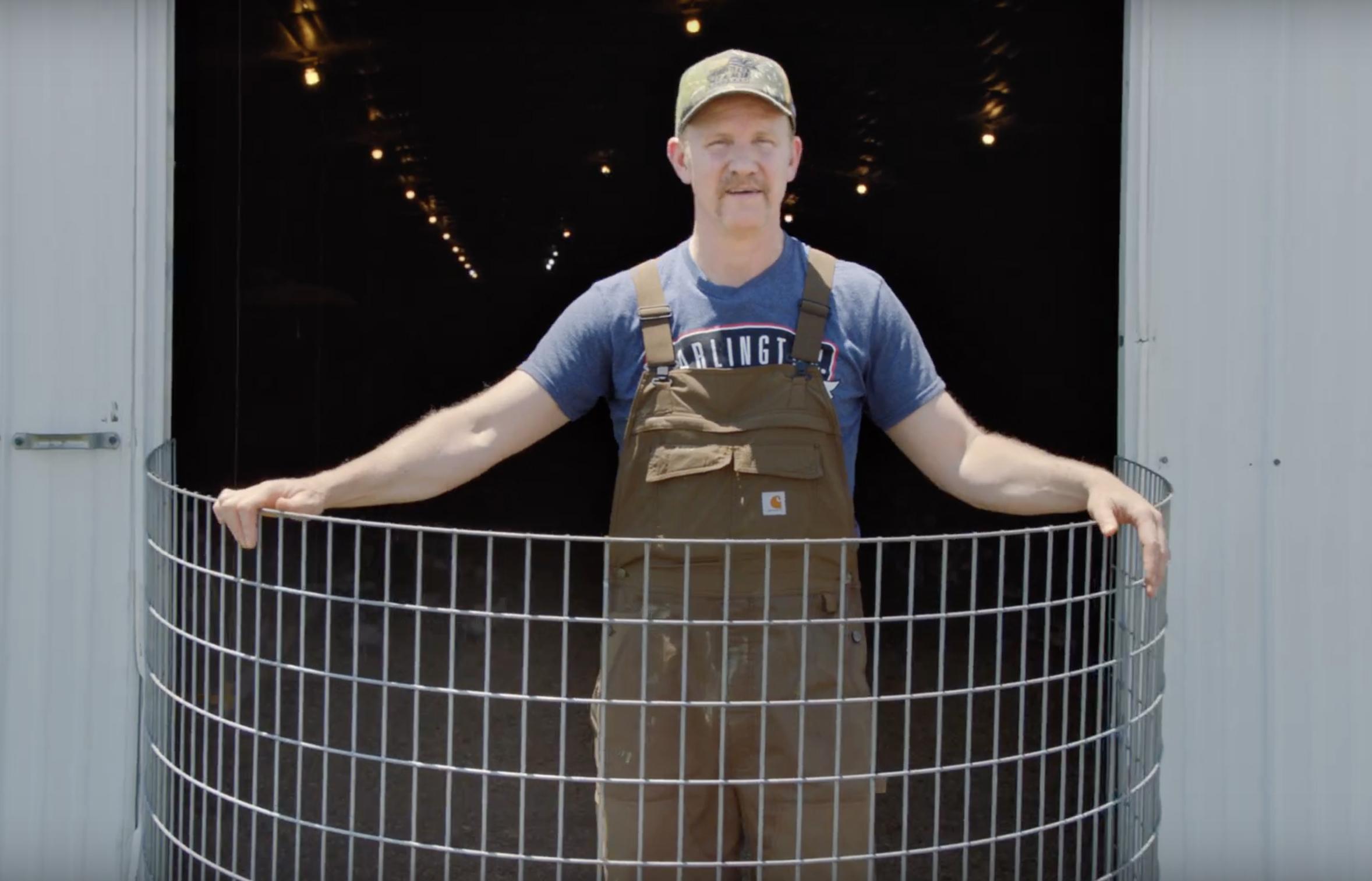 Director Morgan Spurlock wearing overalls, standing in the doorway of his chicken farm