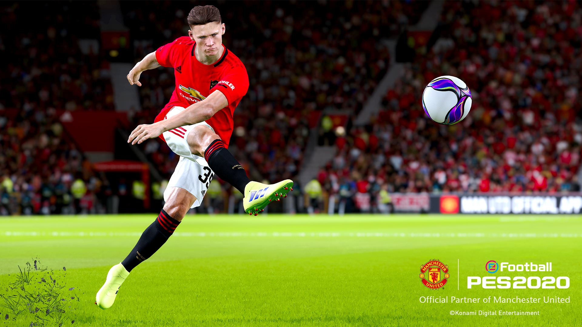 A player for Manchester United takes a strong kick across his body, launching the ball high in the air