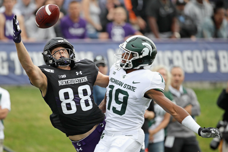 Northwestern receiver Bennett Skowronek tries to catch a pass while being defended by Michigan State's Josh Butler on Saturday in Evanston. Butler was called for pass interference.