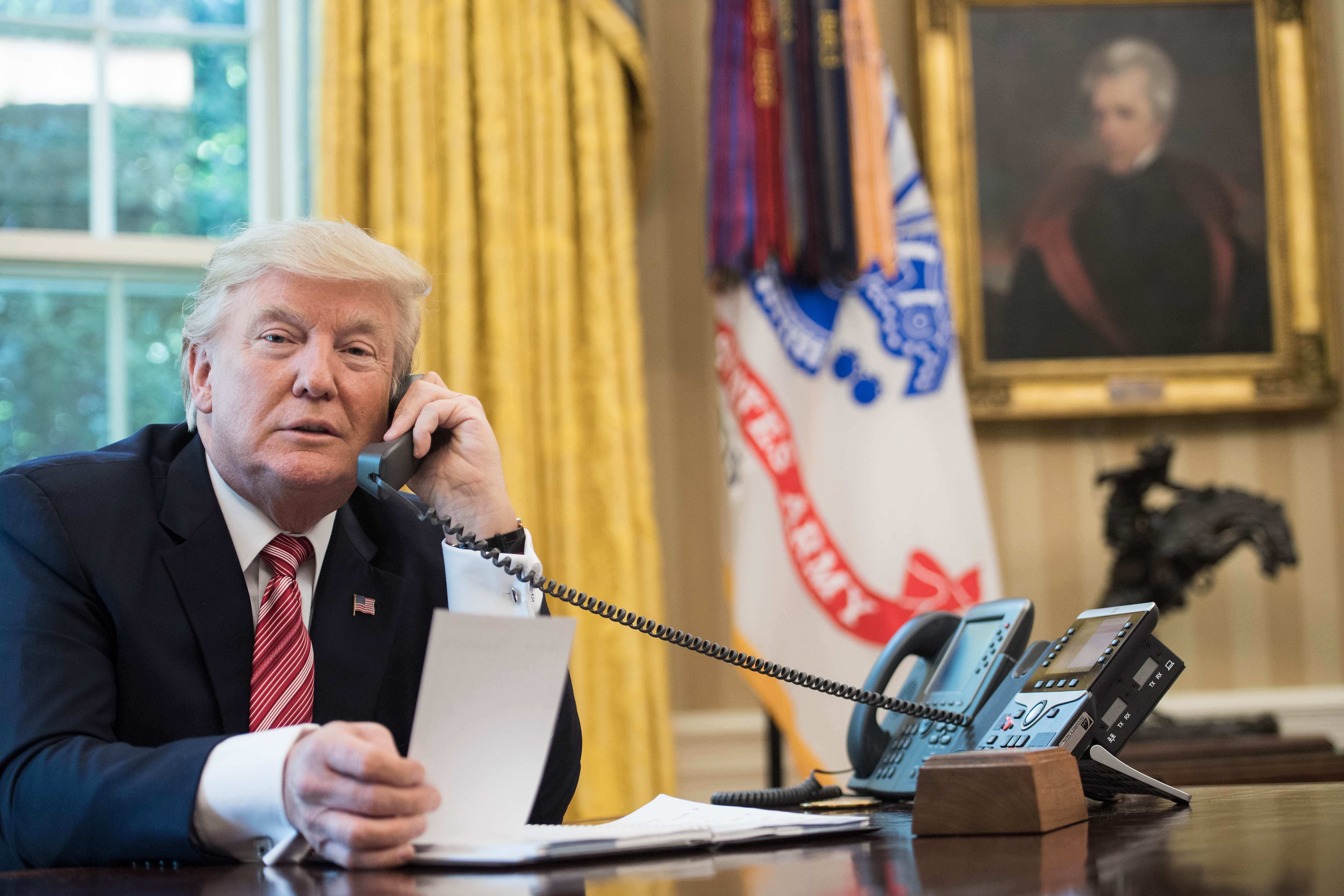 President Donald Trump speaks on the phone in the Oval Office.