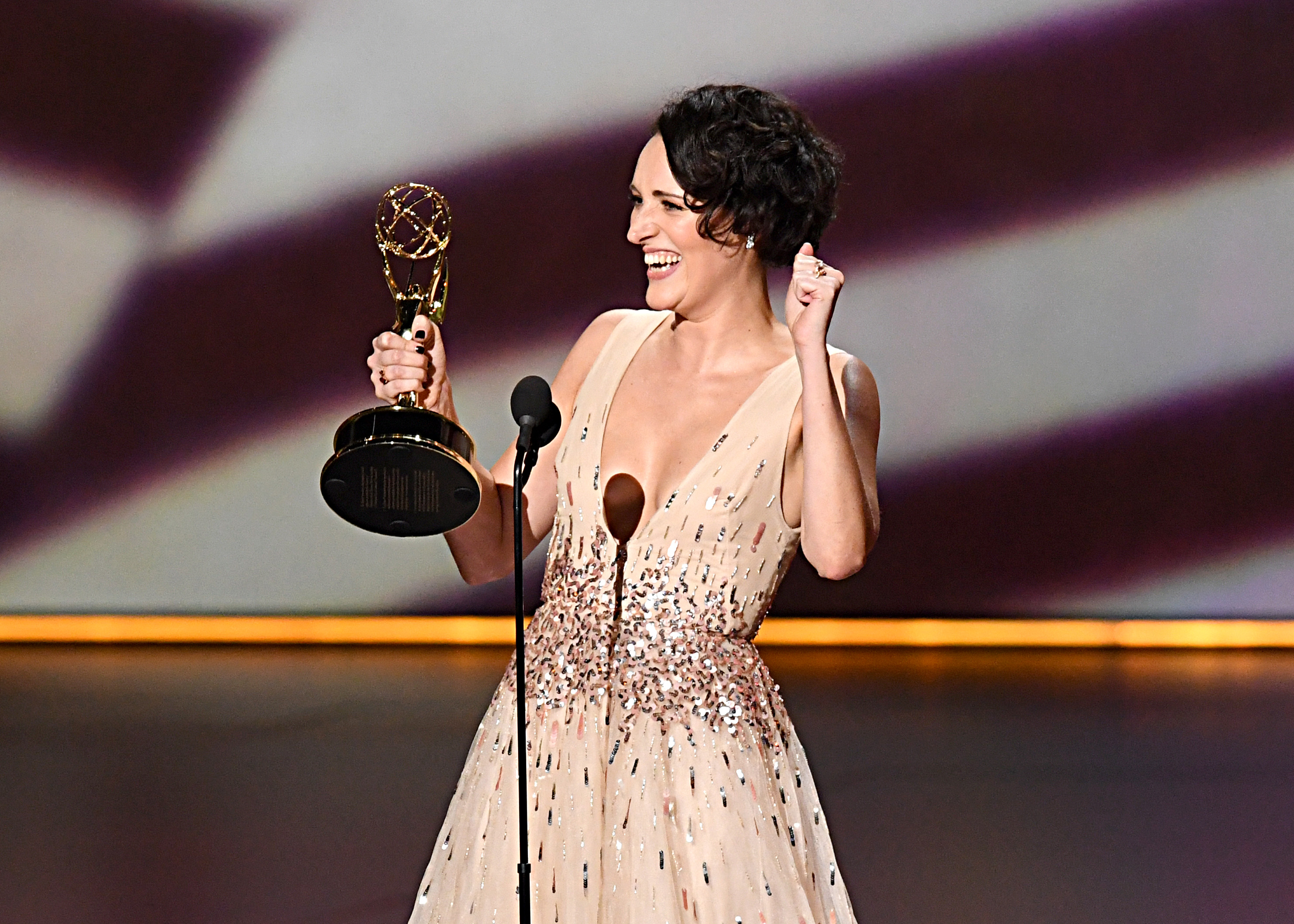 "Phoebe Waller-Bridge of ""Fleabag"" smiles and holds up a fist as she accepts the Emmy for Outstanding Writing for a Comedy Series."