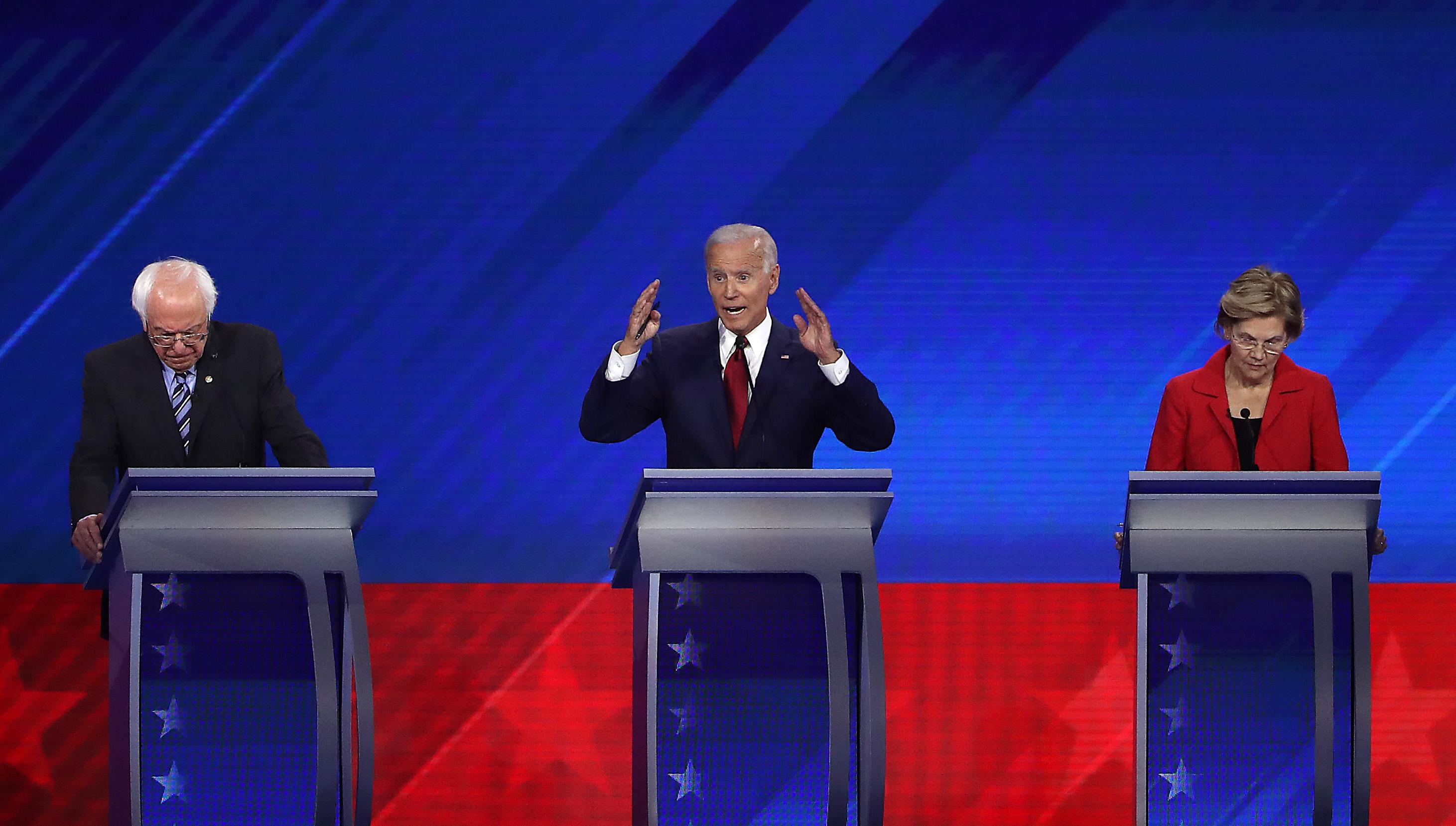 Biden, at the center podium, speaks with his hands up, while Sanders to his right and Warren to his left look down at their podiums.
