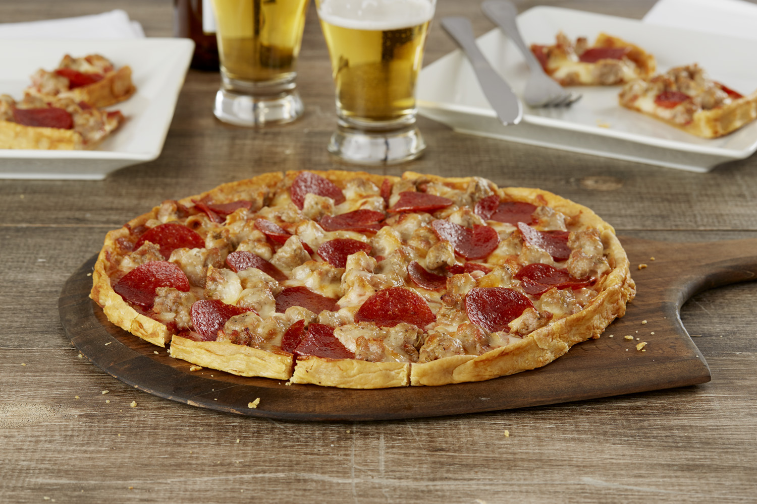 A thin-crust, square-cut tavern-style pizza with pepperoni and sausage on a wooden board with two glasses of beer behind it.