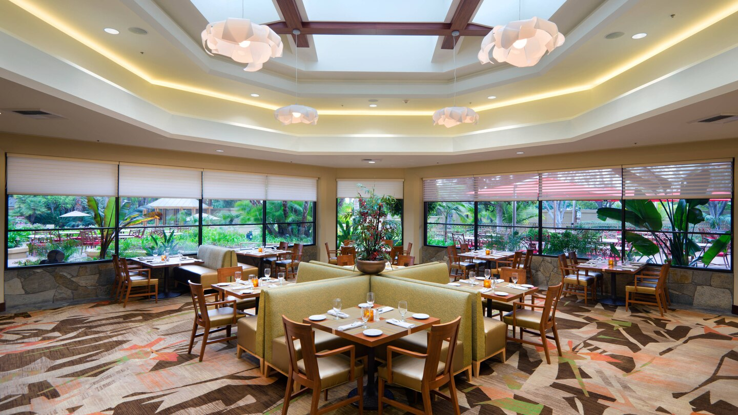 A carpeted dining room inside a hotel with lots of greenery out the windows.
