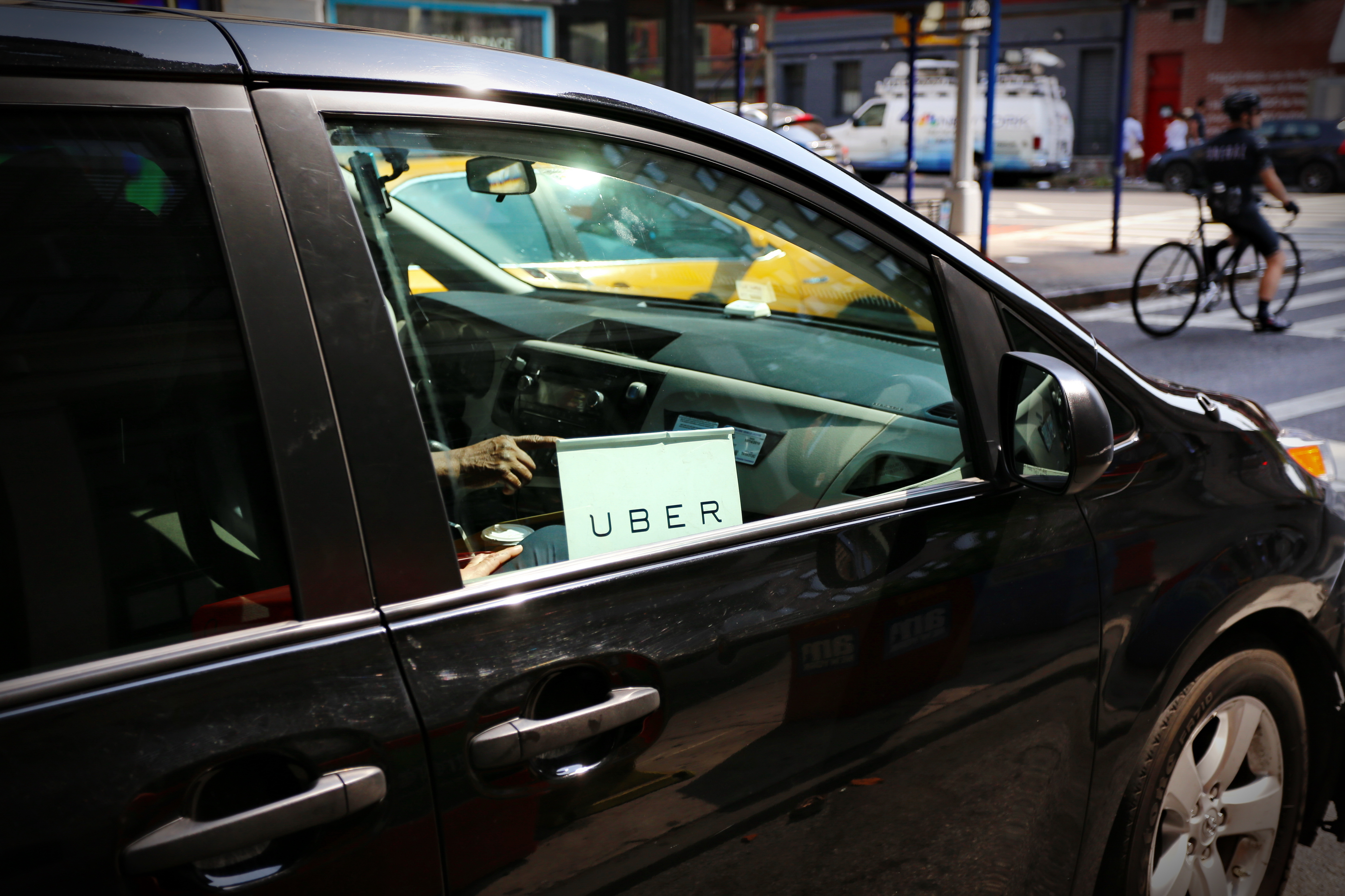 """The passenger side of a black SUV with an """"Uber"""" sign in the window."""