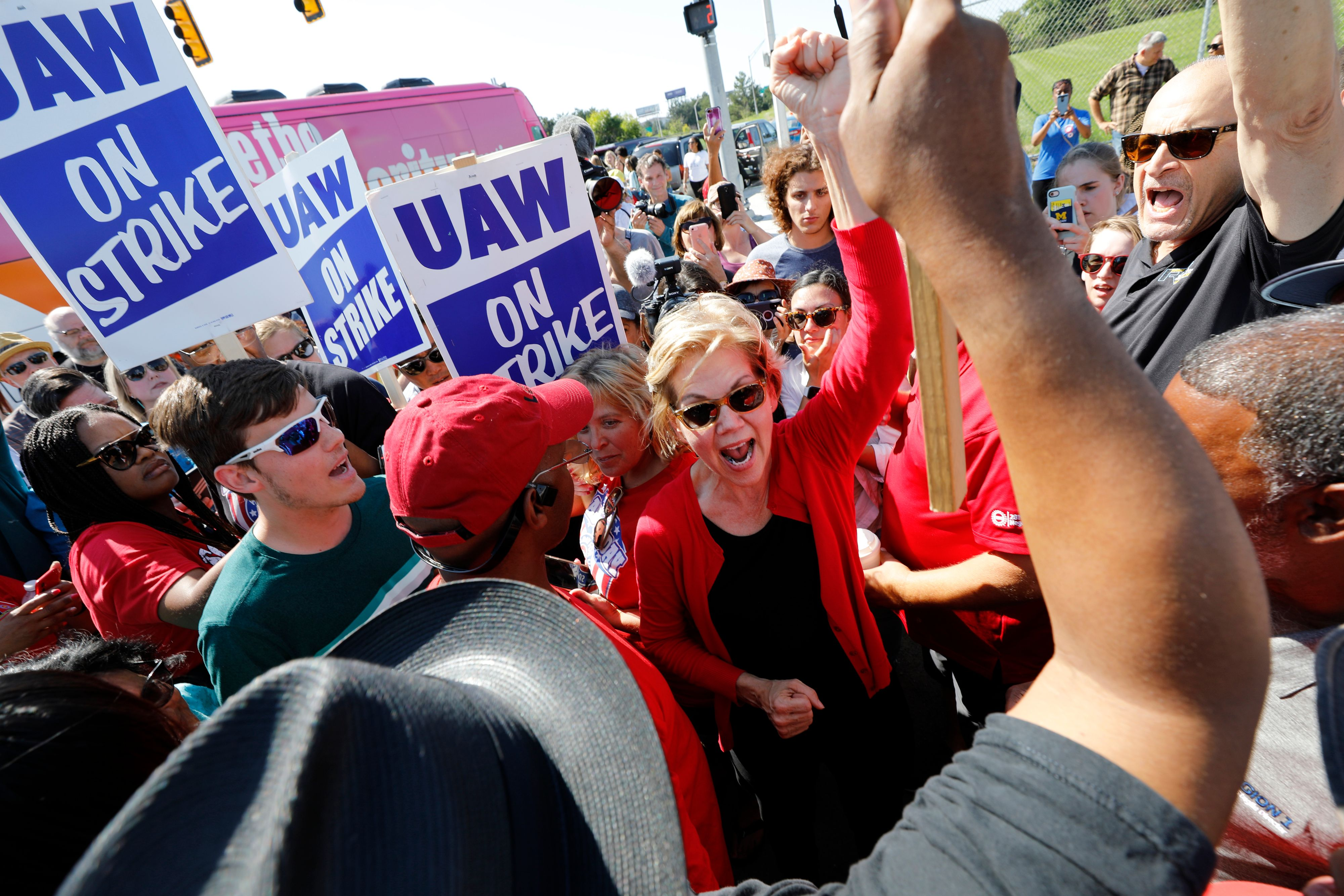 Elizabeth Warren raises her fist in the air while GM workers swarm around her carrying picket signs.