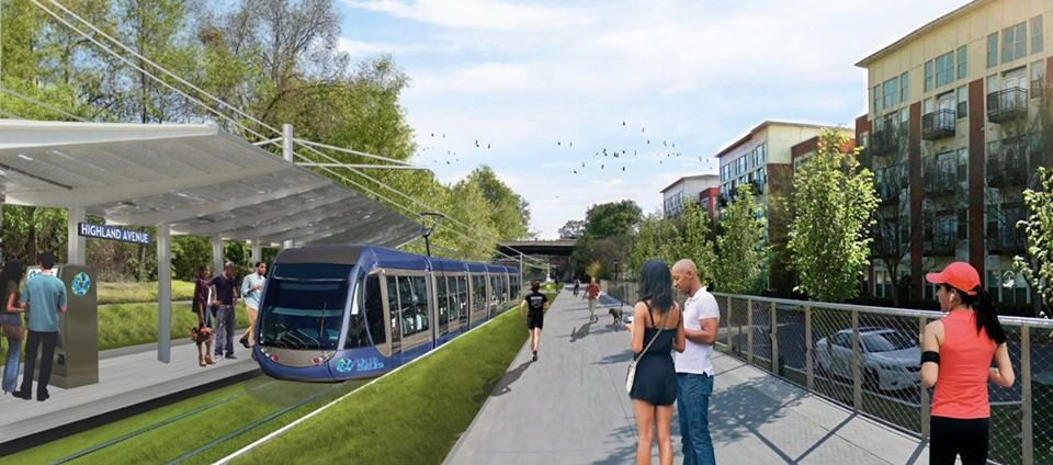 A light rail train is seen on grassy track with a wide multiuser path beside it.