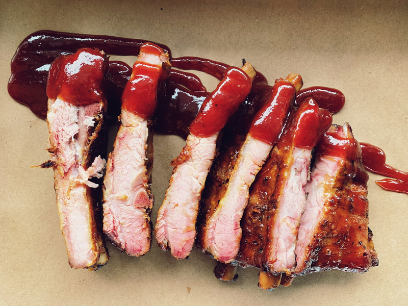 Sliced smoked ribs drizzled in red barbecue sauce sit on a piece of brown paper
