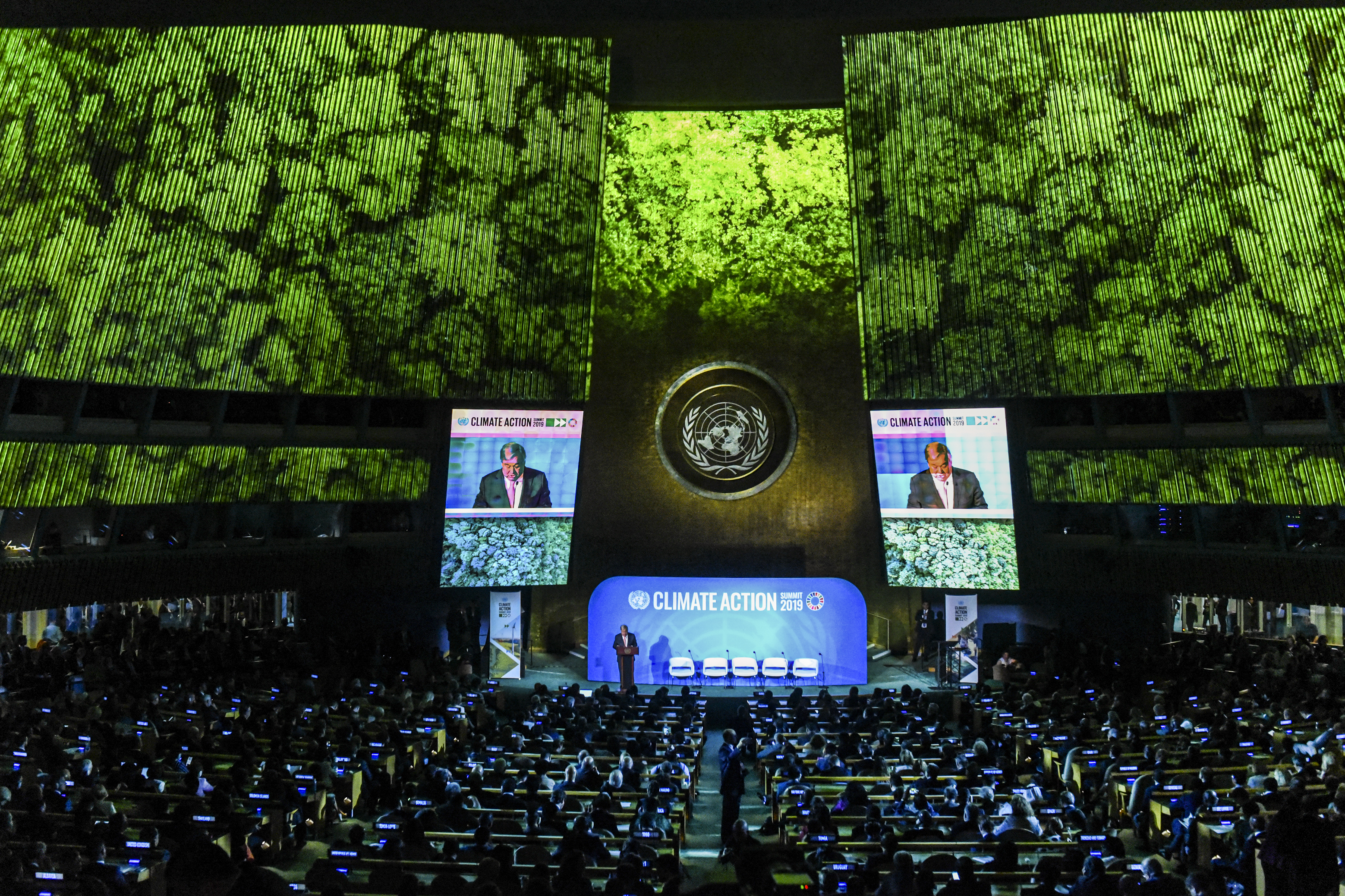 Inside the United Nations Climate Action Summit, where the audience watches two large video monitors flanking UN Secretary-General António Guterres onstage.