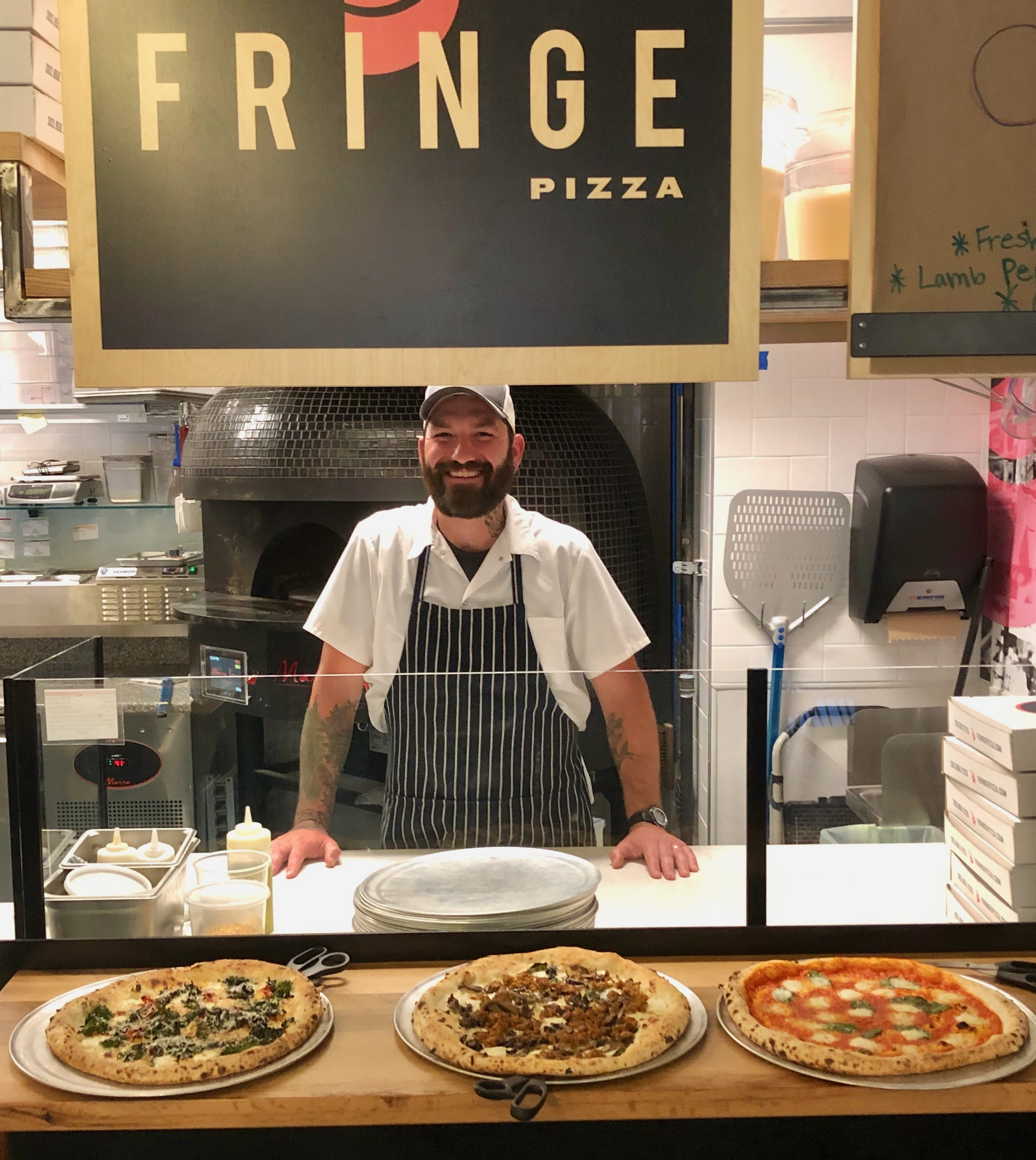 A photo of Nate Rajotte standing behind the counter at Fringe Pizza with three pizzas covered with varying toppings in front of him