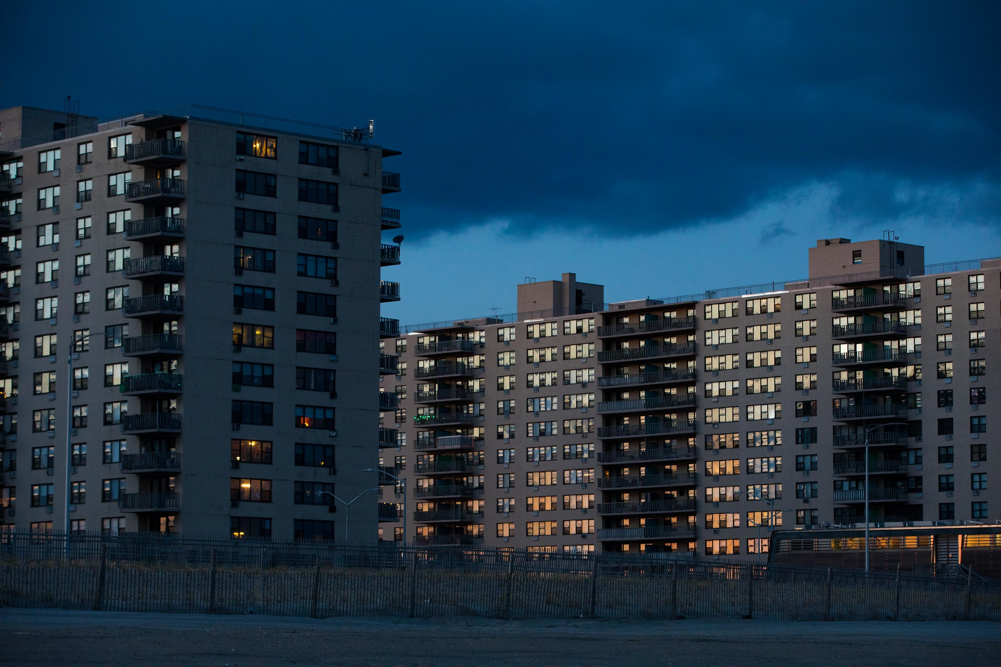 Three high-rise residential towers in Rockaway just off the beach. The setting sun reflects off the windows of the apartments.