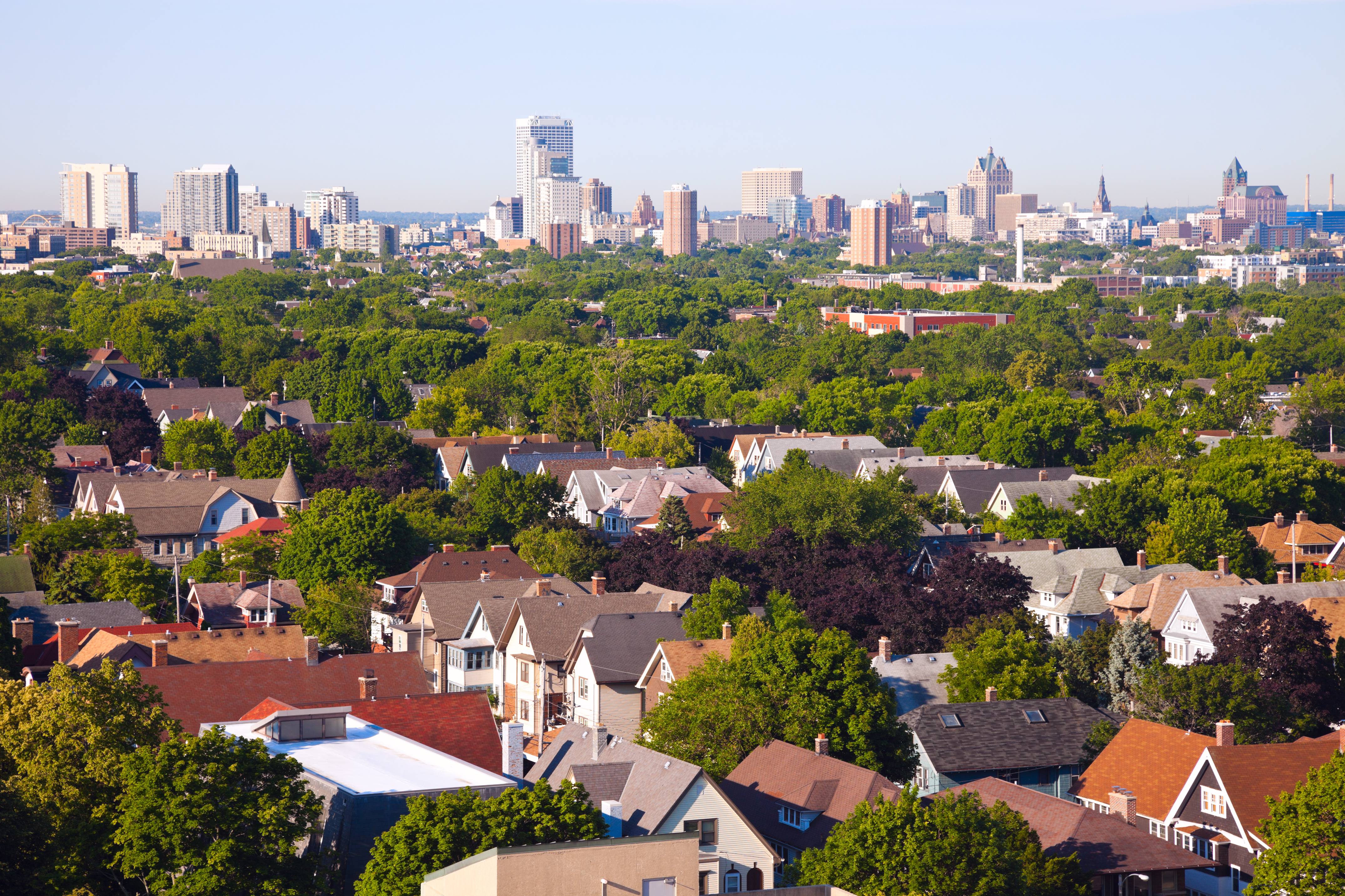 Overhead photo of streets filled with two-story homes and apartments, with a city skyline in the background.
