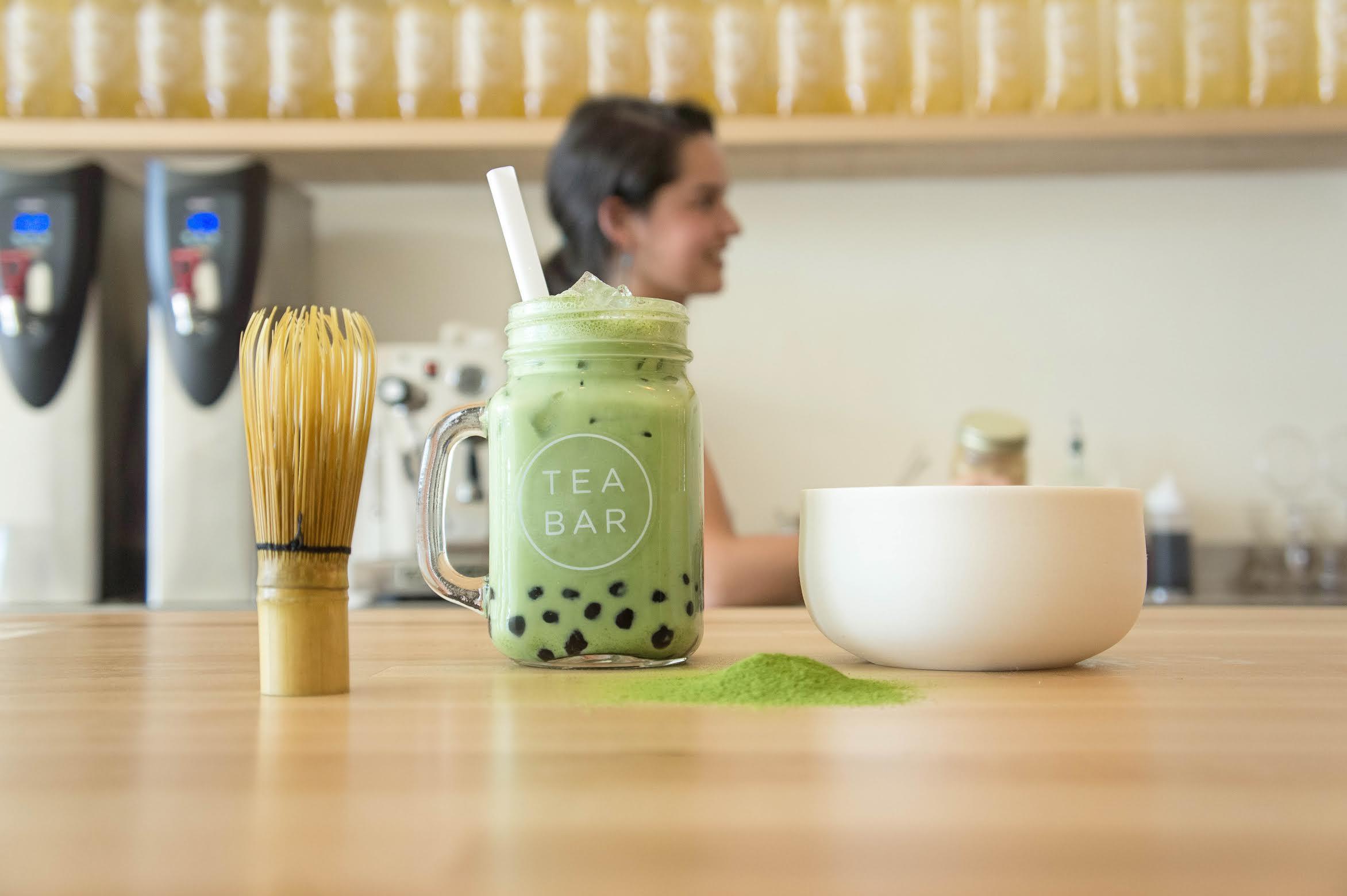 A glass of mint green bubble tea in a glass jar