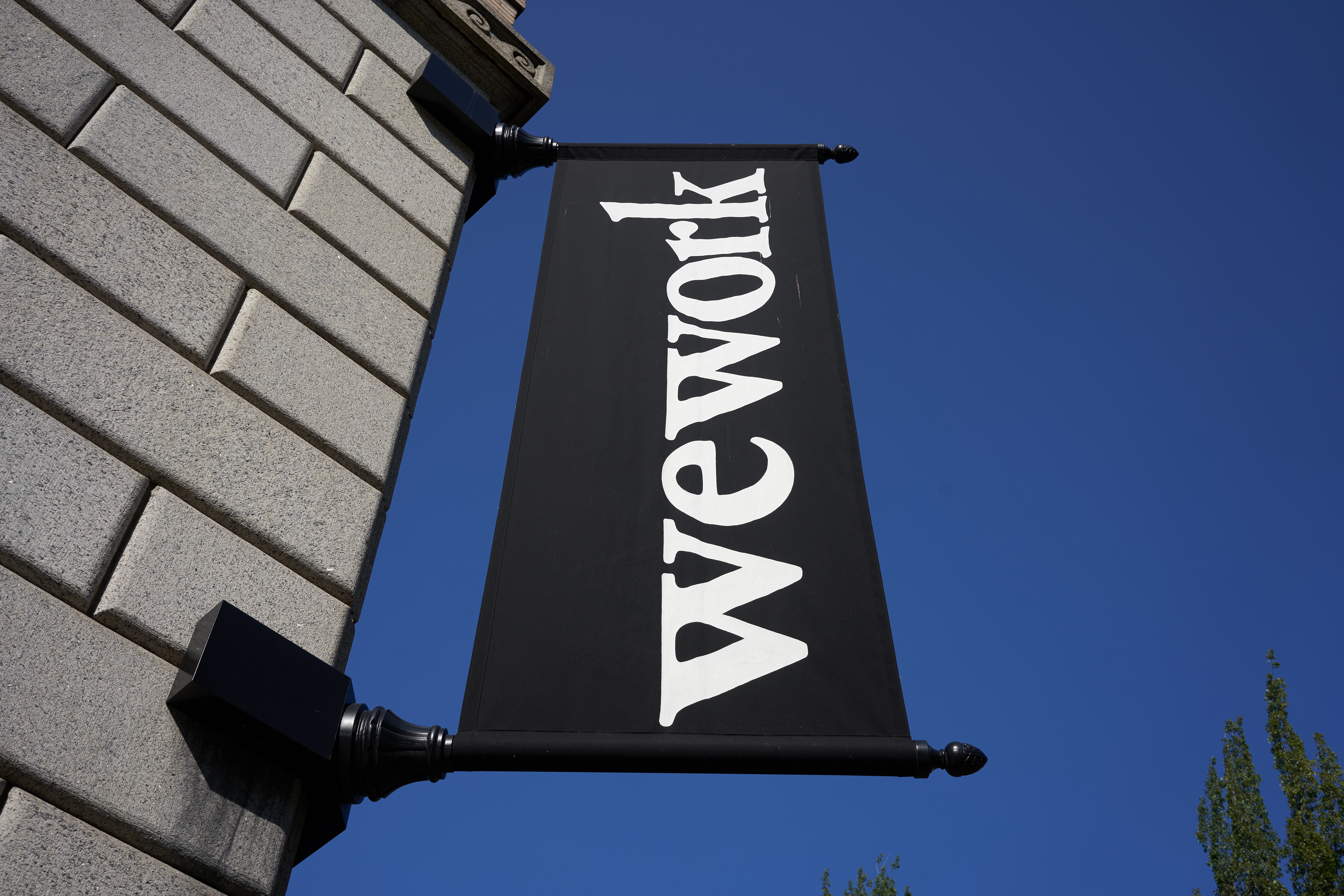 A WeWork banner outside of an office building.