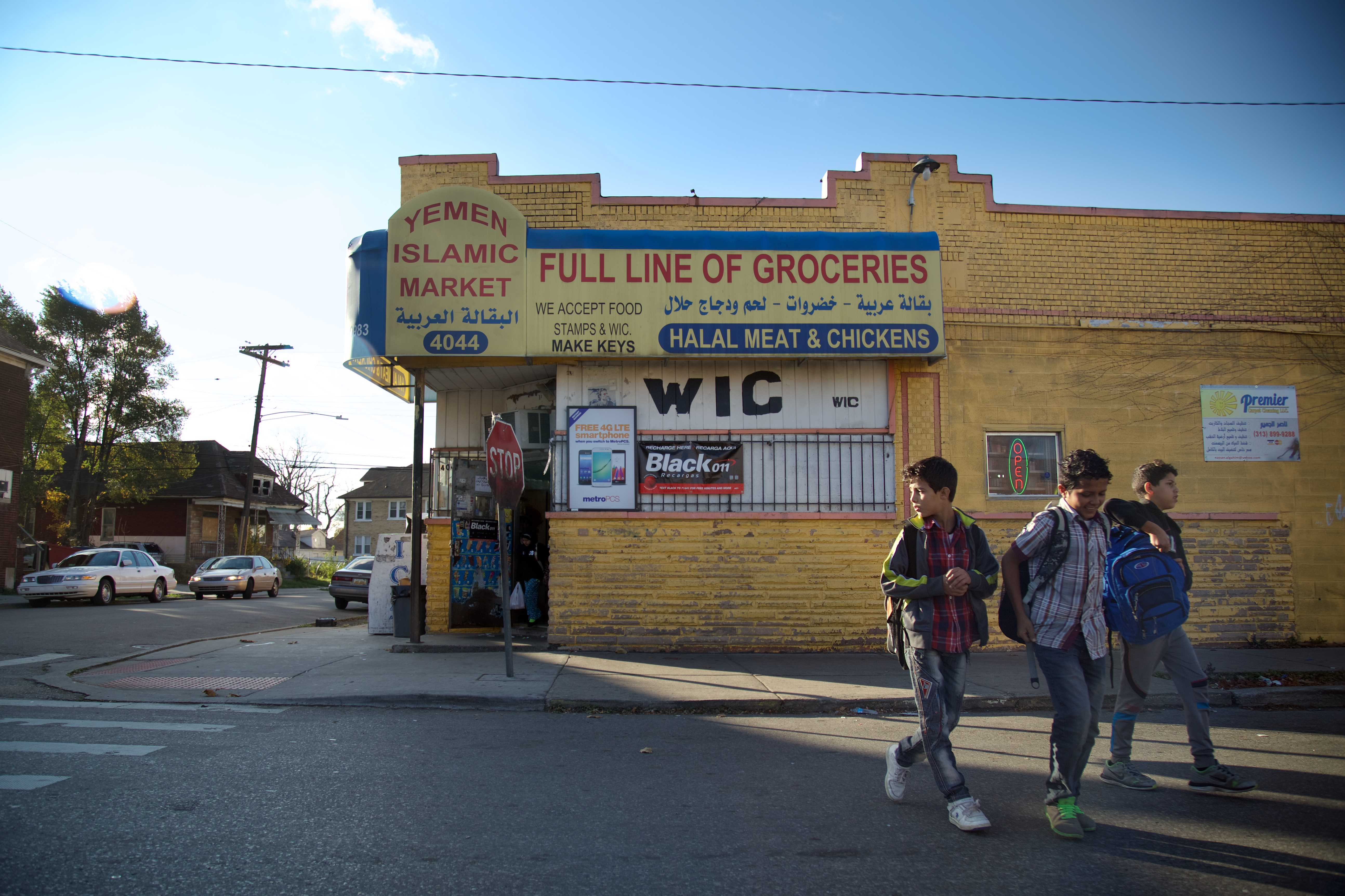 """Three kids walk away from a grocery store with a sign on a yellow awning that reads """"Yemen Islamic Market."""""""