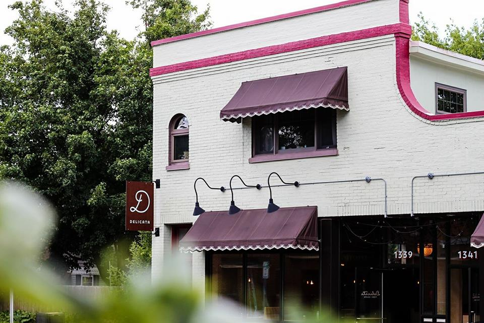 The gray exterior of the restaurant with maroon awnings