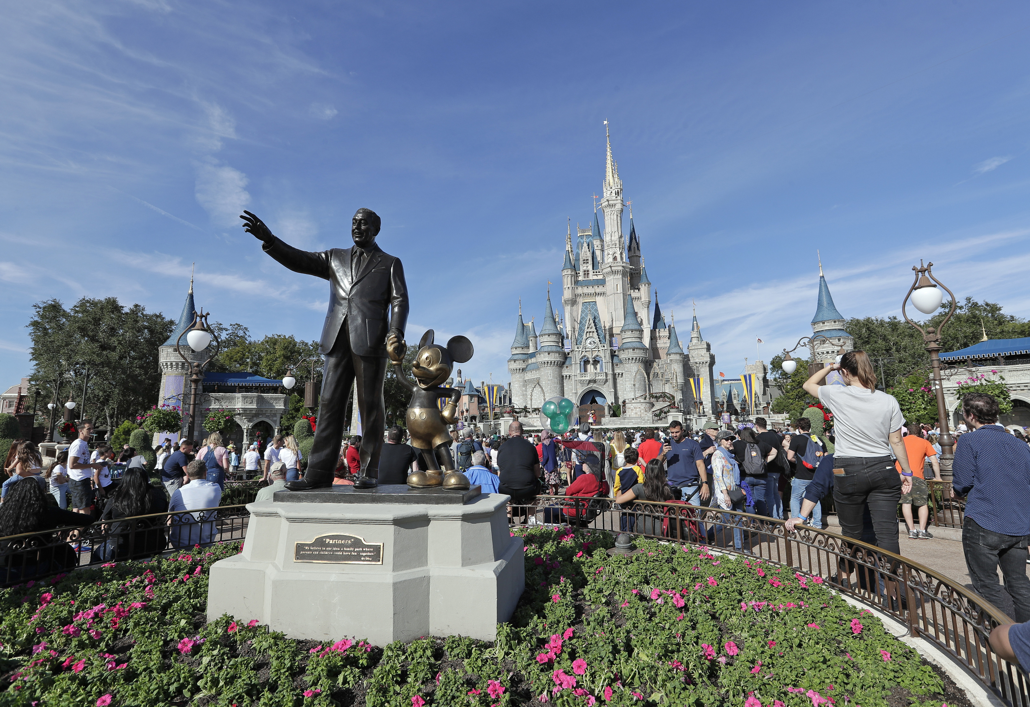 In this Jan. 9, 2019, file photo, theme park guests walk near a statue of Walt Disney and Mickey Mouse in front of the Cinderella castle in the Magic Kingdom at Walt Disney World in Lake Buena Vista, Fla.(AP Photo/John Raoux, File)