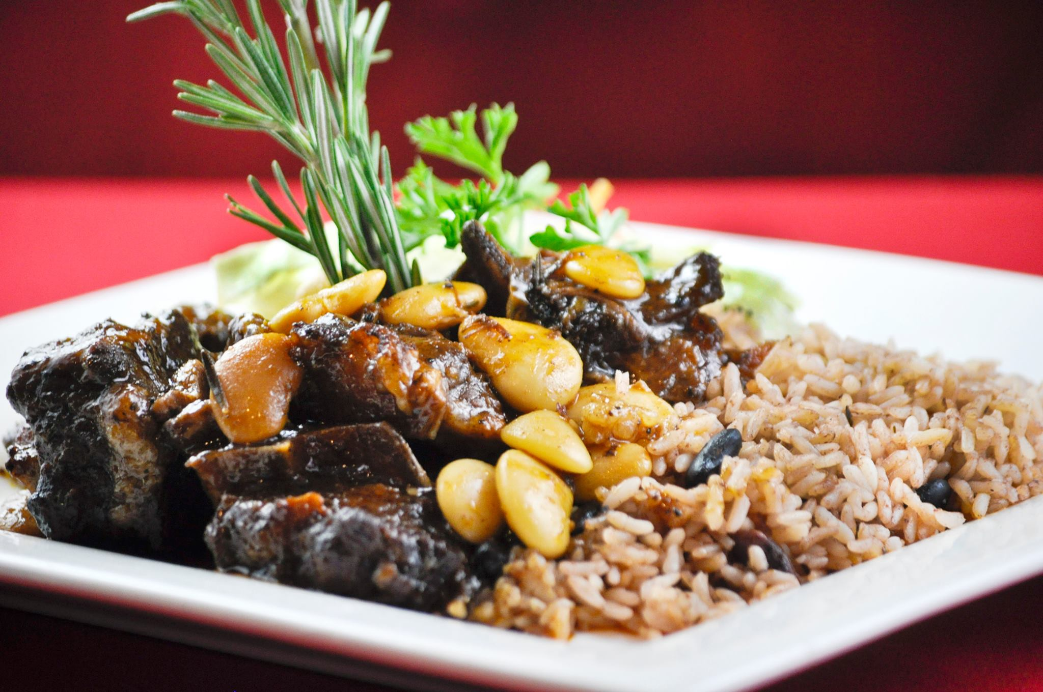 A white platter with braised oxtails, sprig of rosemary, vegetables, seasoned rice, and peas
