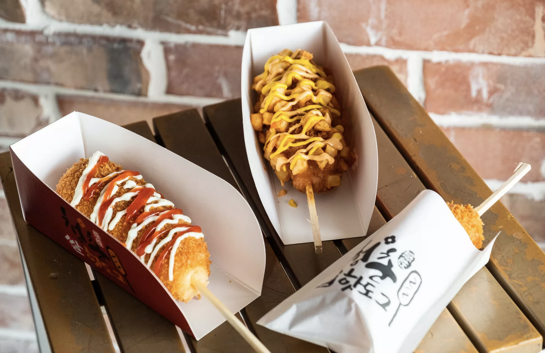A variety of Chung Chun's corndog-like snacks, dressed with a variety of colorful sauces, served in paper trays and wrappers.