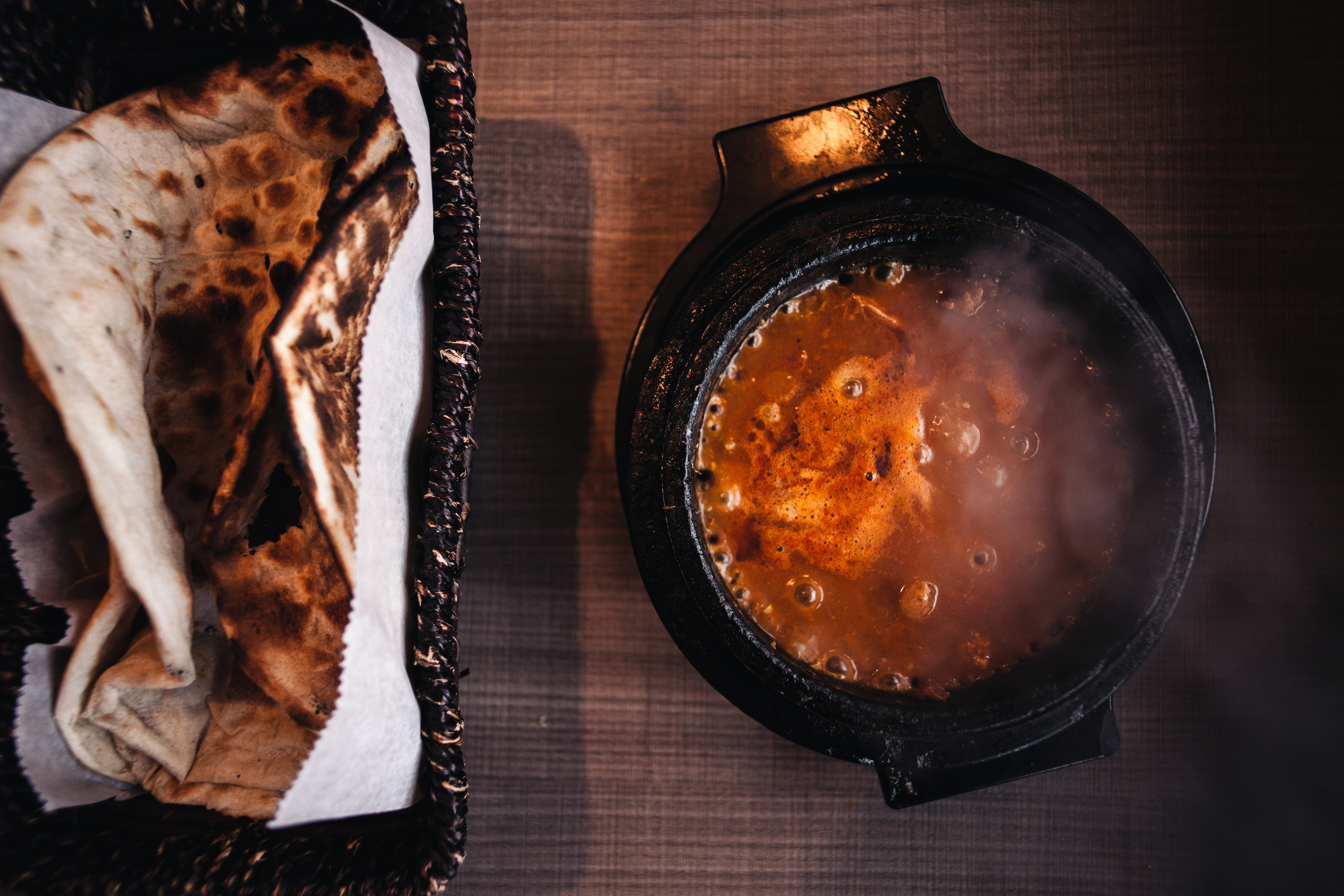 A boiling bowl of a red stew with flatbreads.