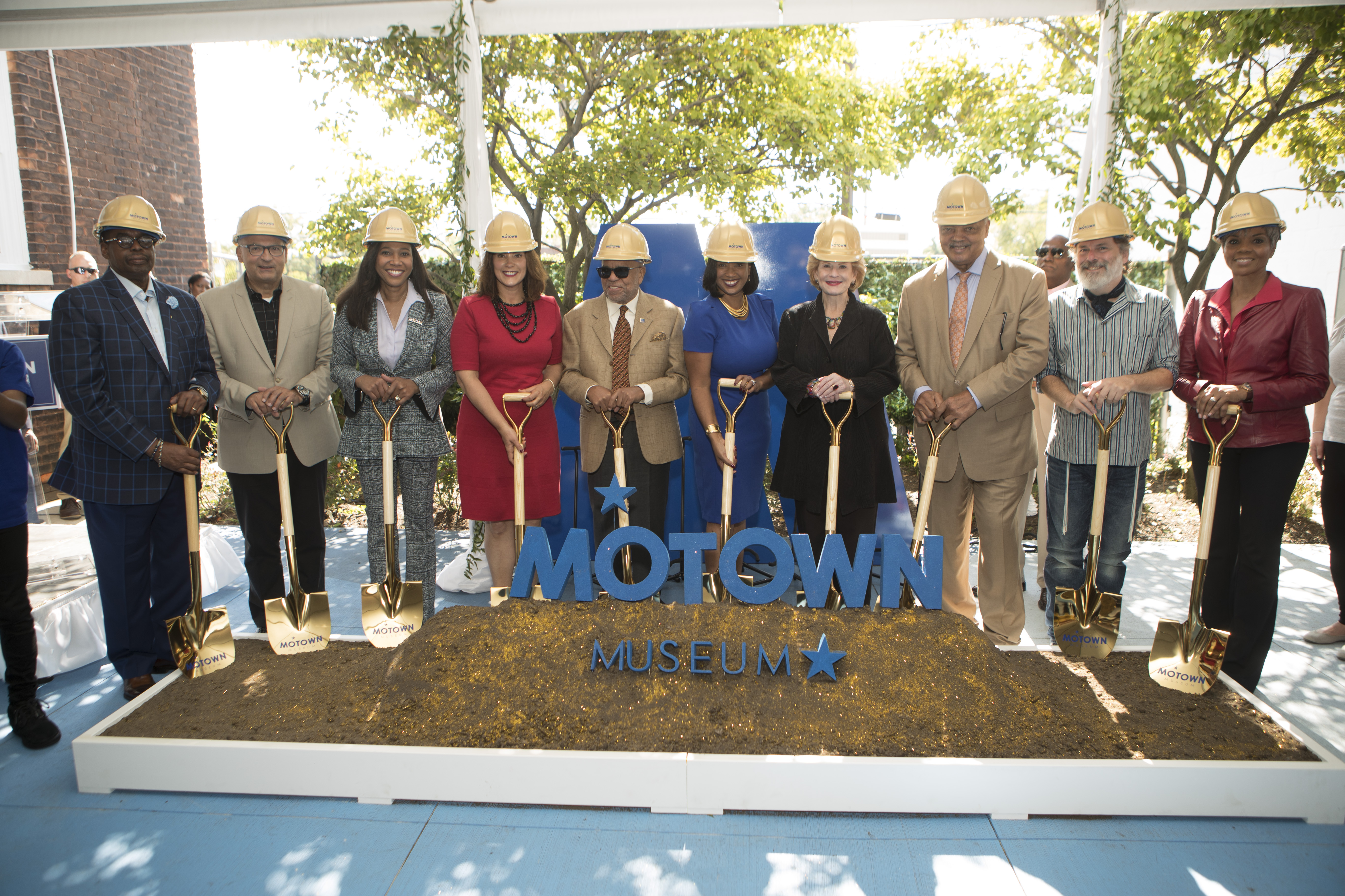 """10 people with shovels and hardhats stand over a mount of dirt with letters reading """"Motown Museum"""" on top."""