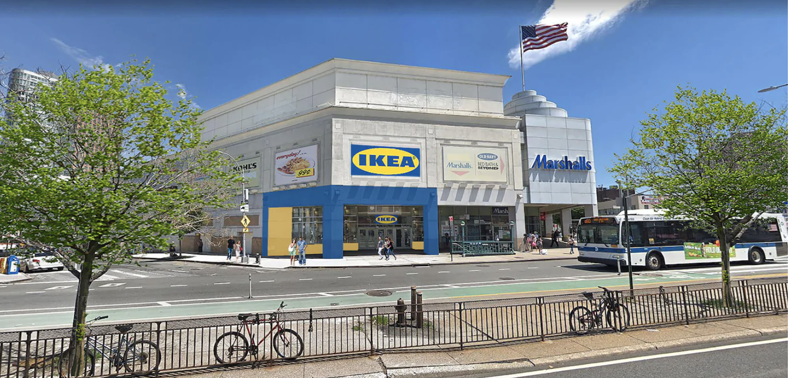 """The view of a mall with and a section that reads """"Ikea"""", next to a Marshall's. A road and a bike line are in front of it."""