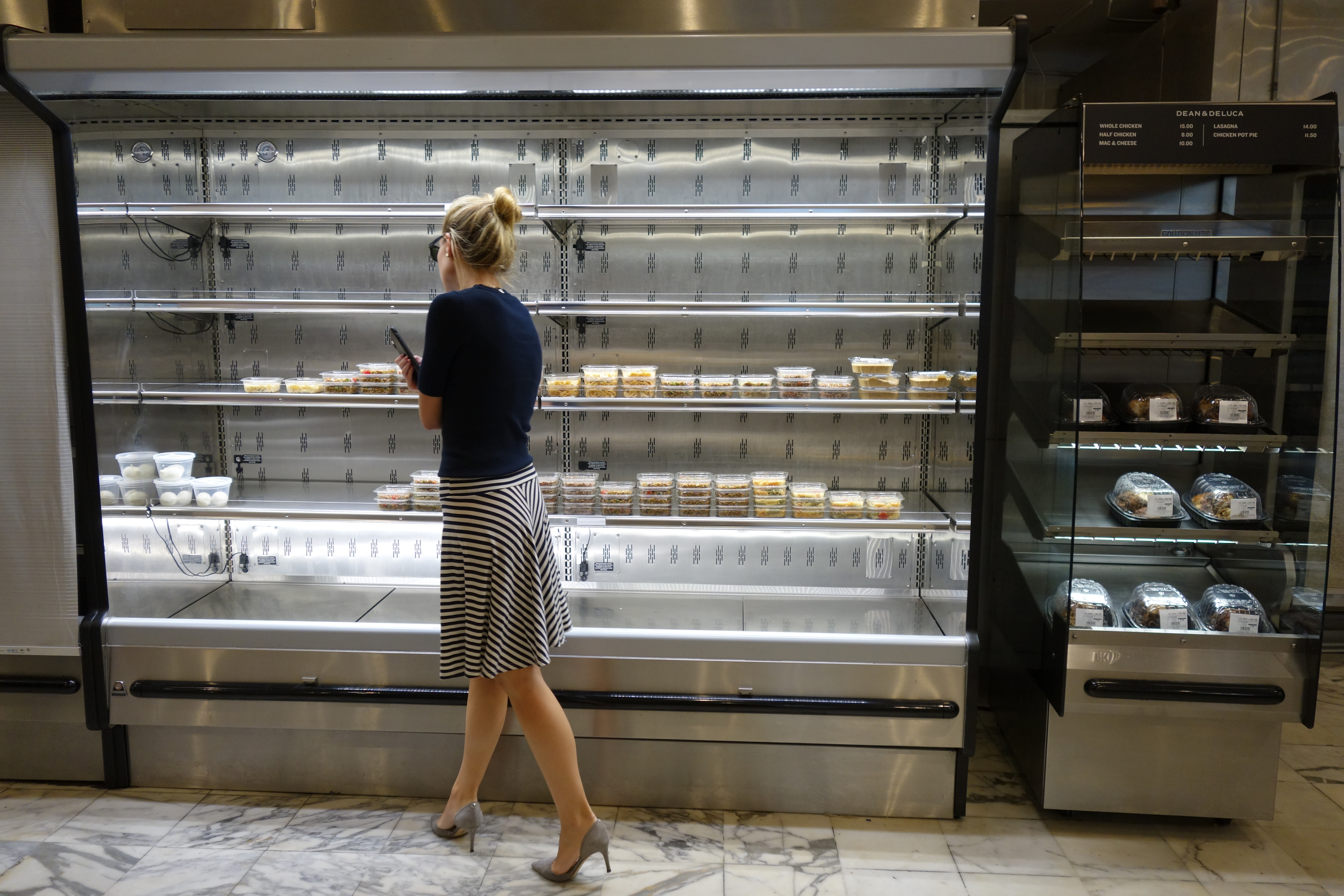 A customer stares at nearly empty shelves where a few to-go foods are available