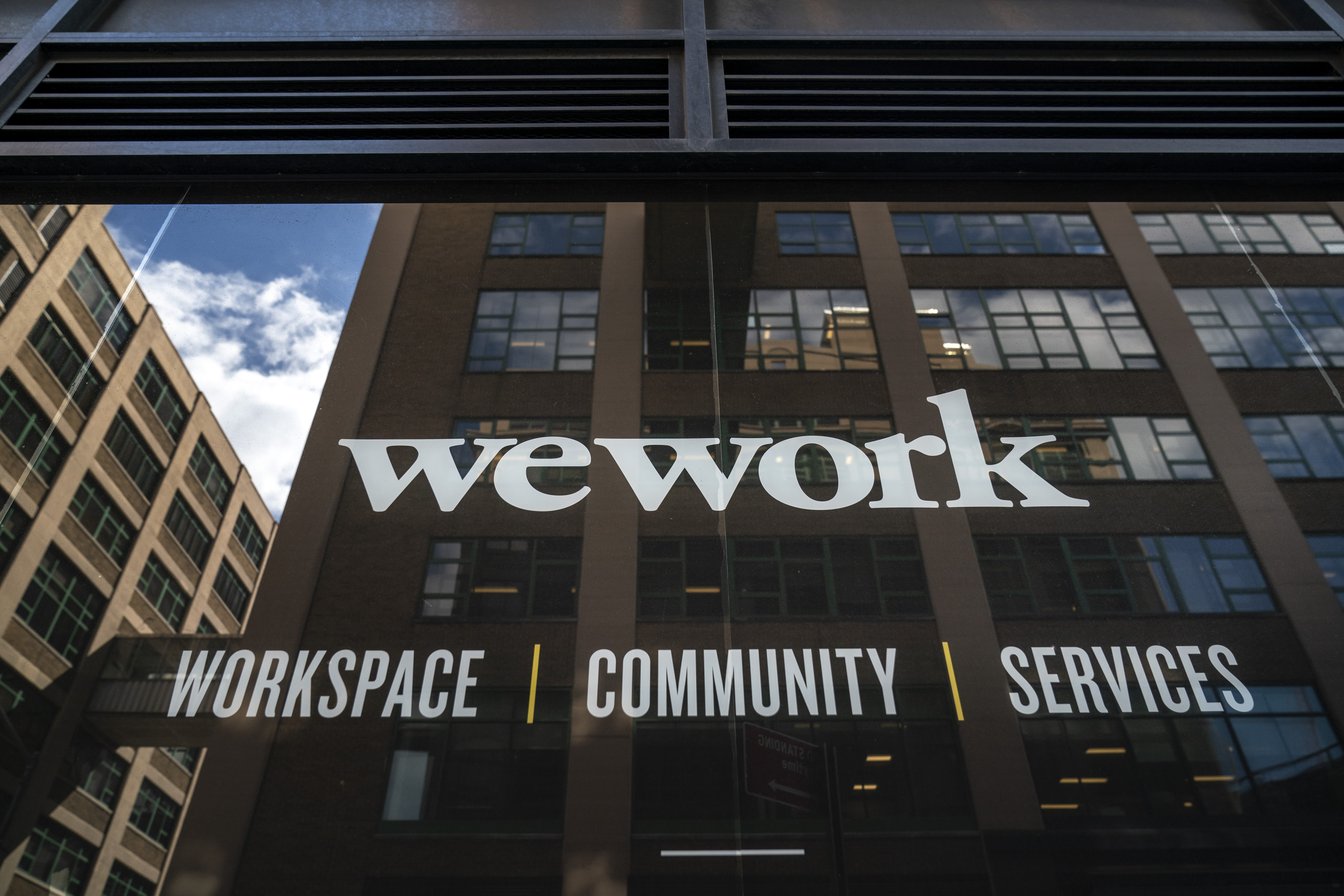 """WeWork sign that reads """"WeWork workspace, community, services"""" on a building in DUMBO, Brooklyn, with other buildings and the sky reflected in it."""