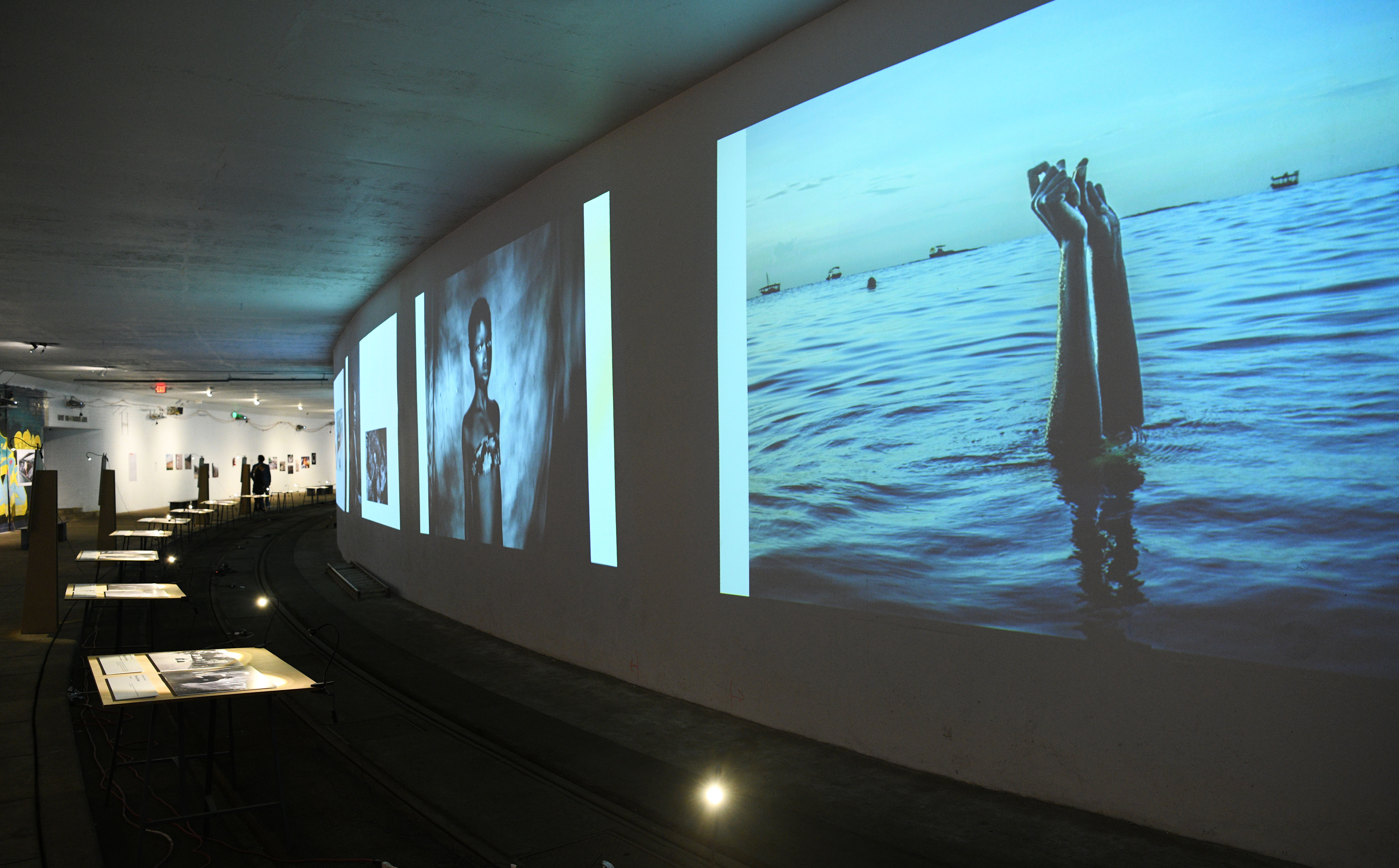 A photo exhibition displayed along the walls of an underground tunnel. One of the photos shows a pair of arms reaching up from a body of water.
