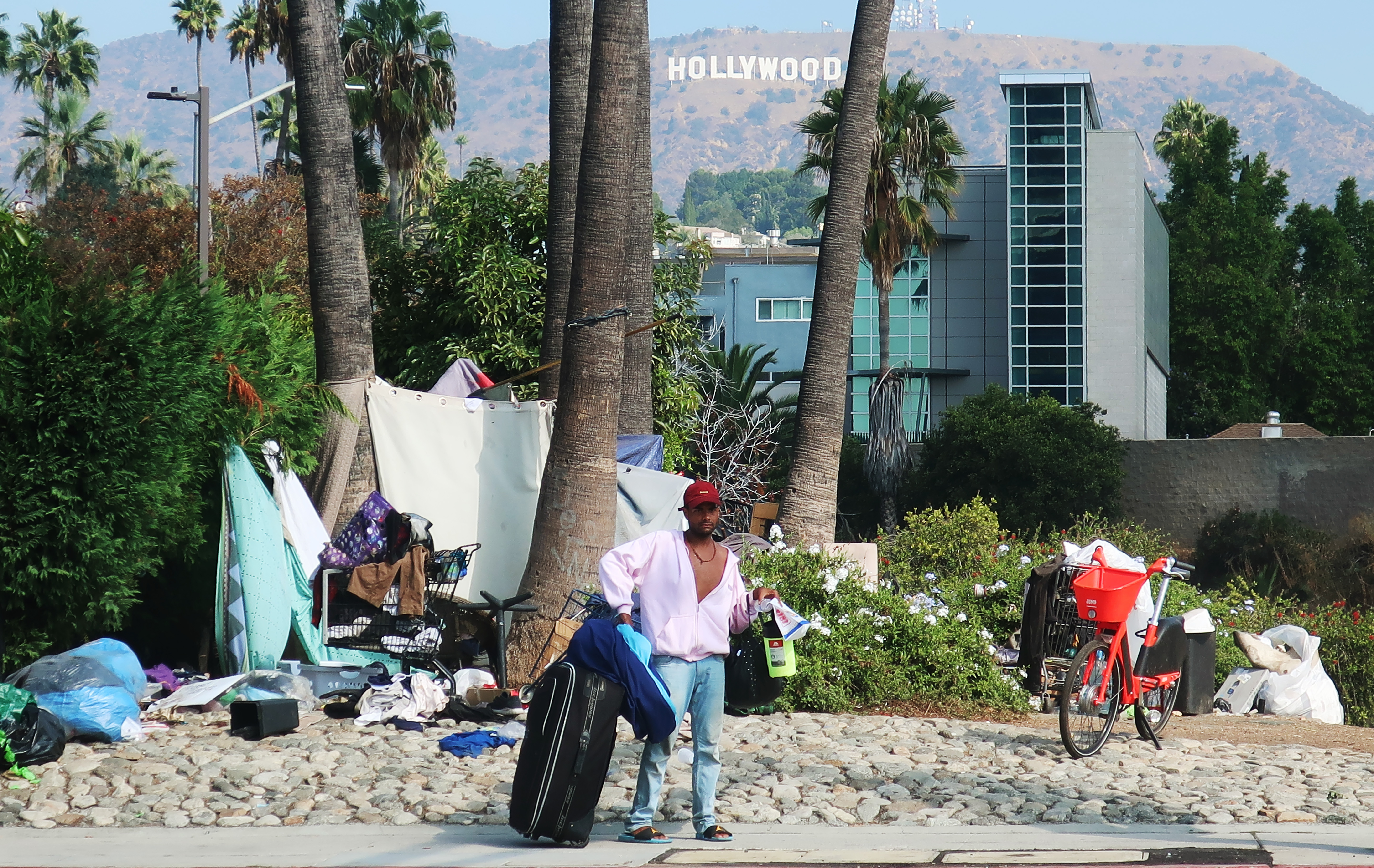 A slender man in a partially unbuttoned pink shirt, blue jeans, and a red baseball cap stands with a black rolling suitcase in front of tents, tarps, and shopping carts. Buildings, palm trees, hills, and the Hollywood Sign in the background.