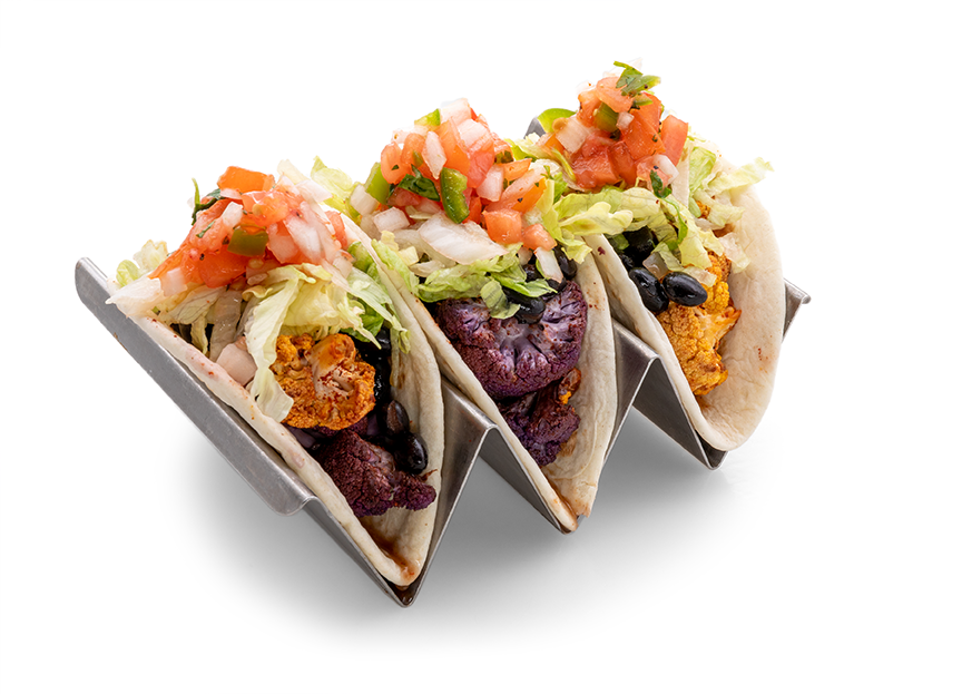 A photo of a metal holder containing three of Empower Field's new vegetarian street tacos. A layer of Chipotle roasted cauliflower and ranchero black beans are visible inside the flour tortillas. They are topped with lettuce and salsa.
